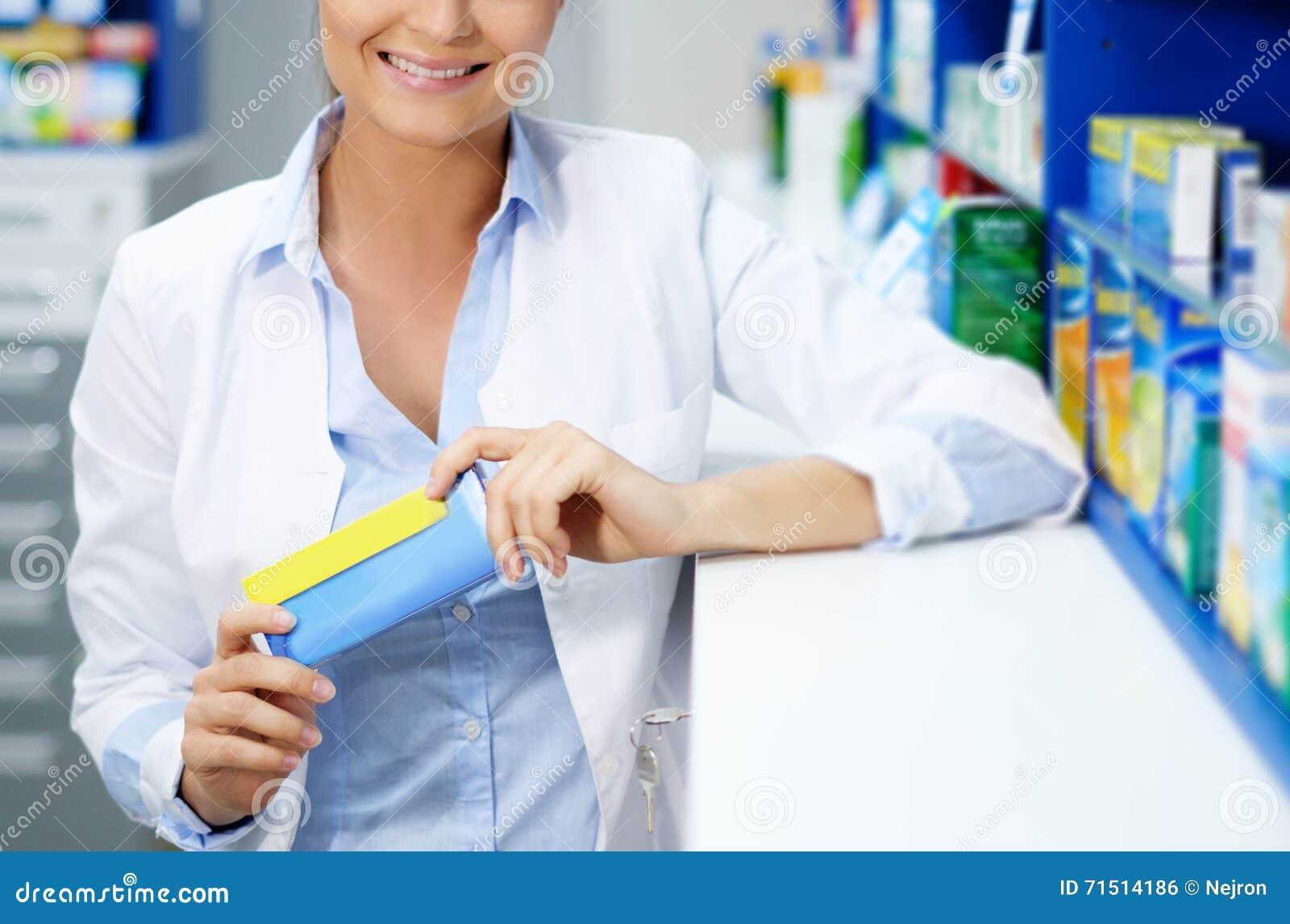 Härligt kvinnaapotekareanseende på hennes arbetsplats i apotek