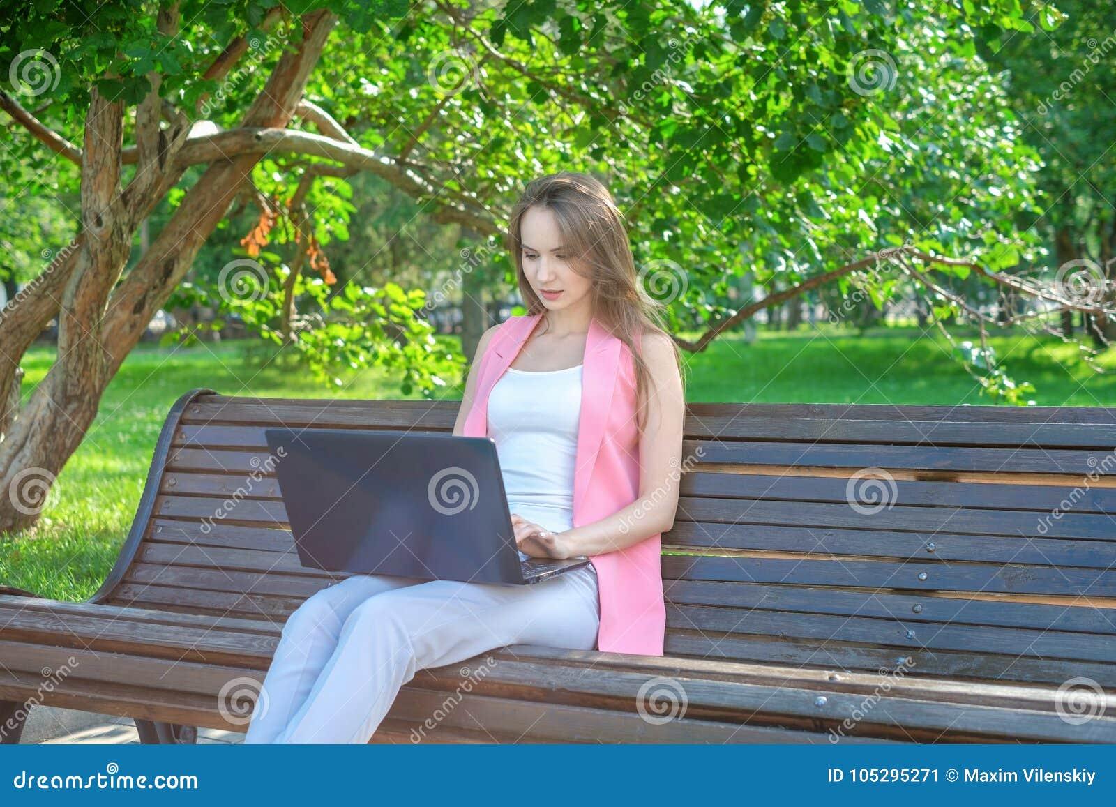 Härligt kvinnasammanträde på en parkerabänk genom att använda en bärbar dator