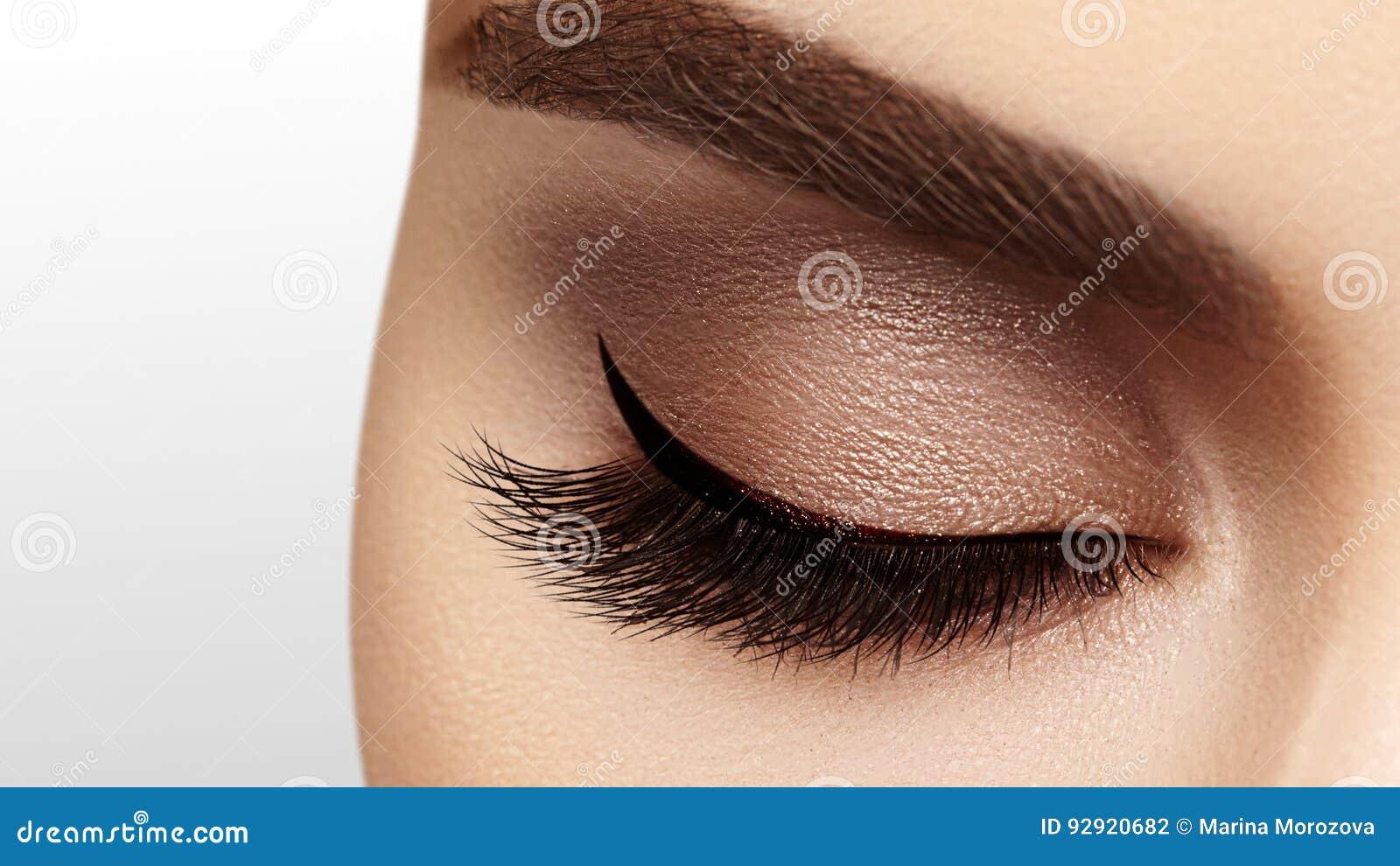 Härligt kvinnligt öga med extrema långa ögonfrans, svart eyelinermakeup Perfekt smink, långa snärtar Closeupmodeögon