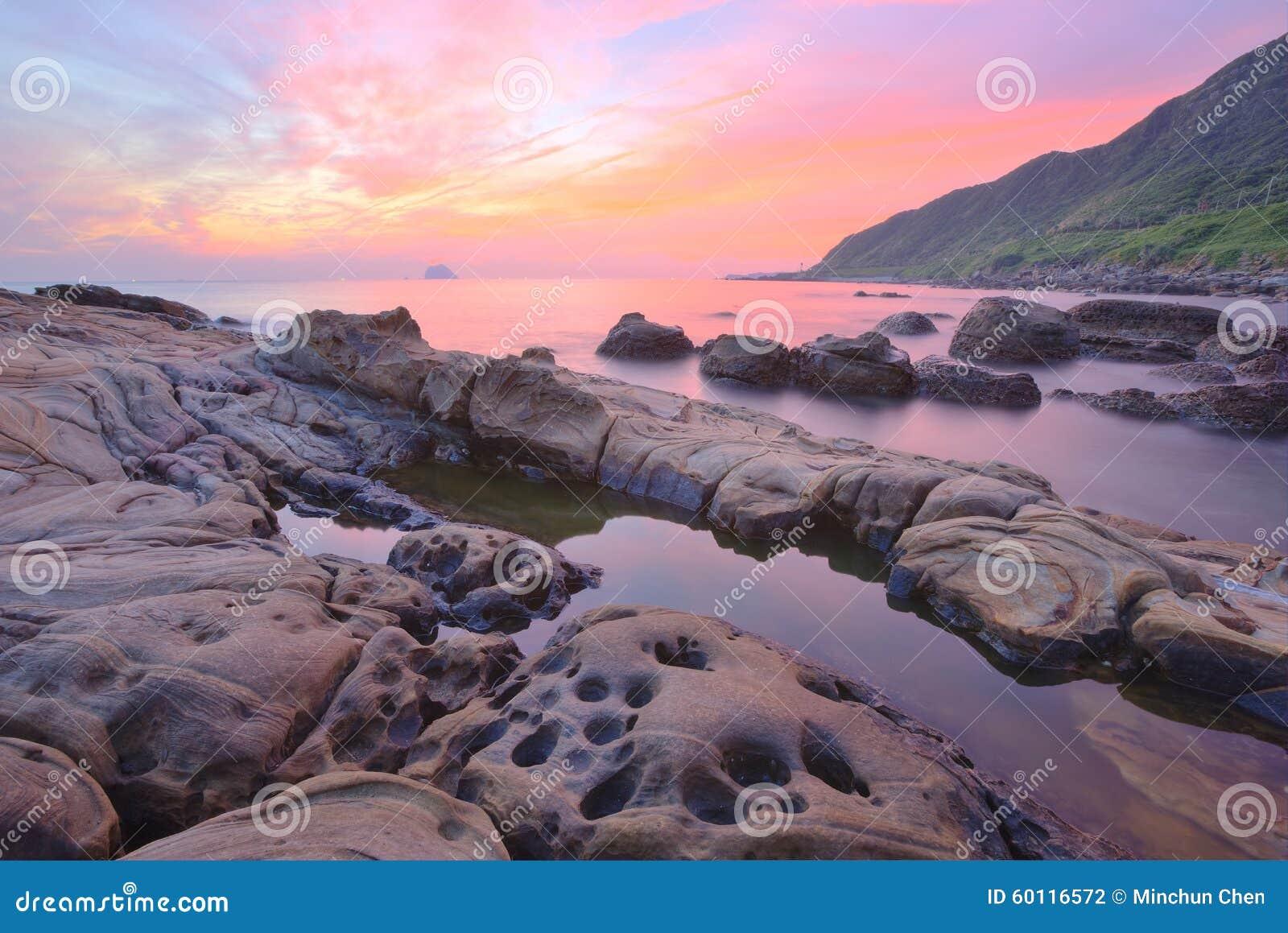 Härligt landskap av att gry himmel vid den steniga kusten i nordliga Taiwan (lång exponeringseffekt)