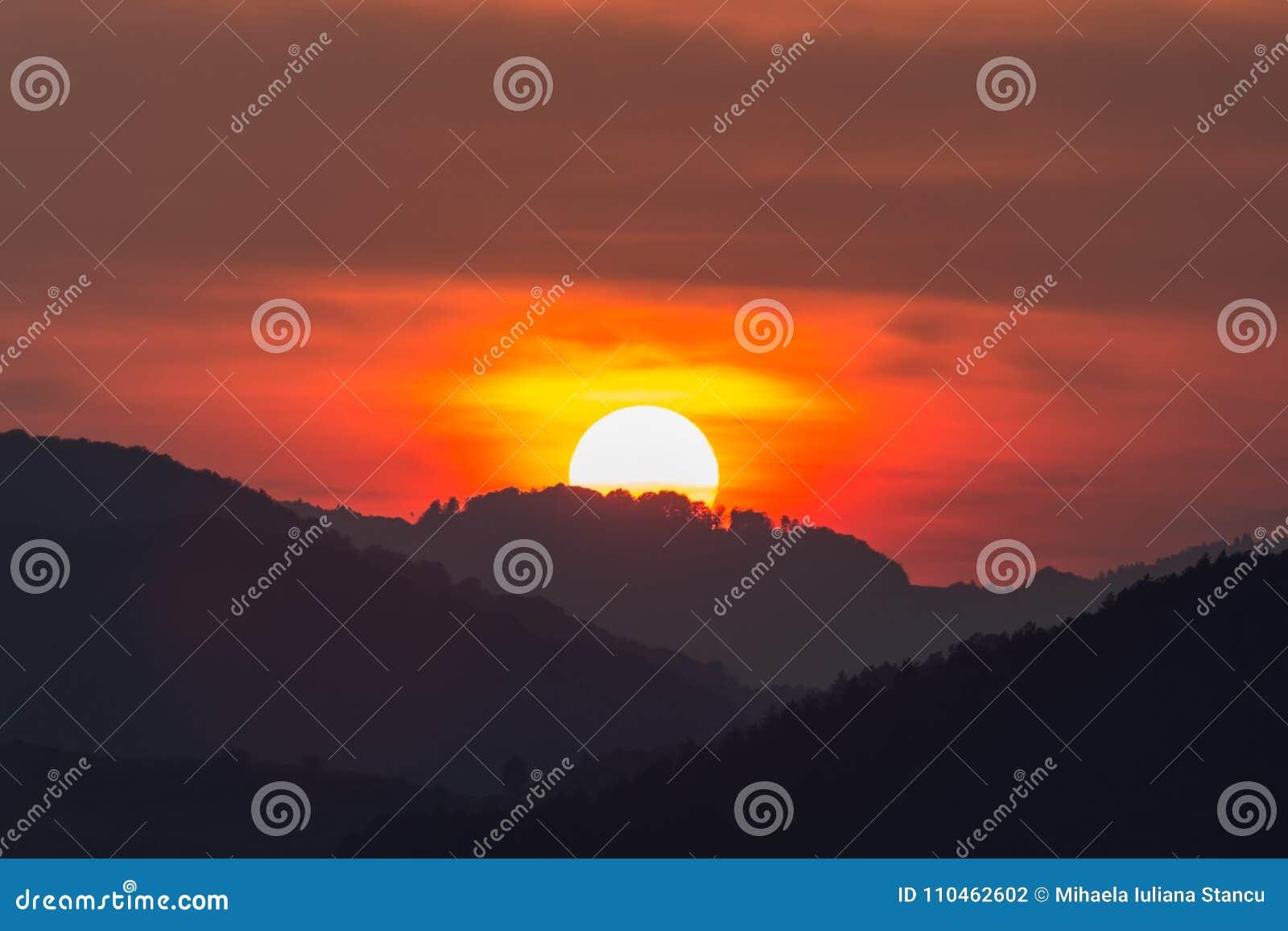 Härligt landskap av en stor inställningssol över konturn av bergen