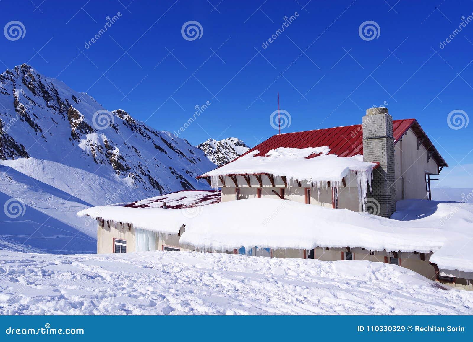 Härligt landskap med den alpina kabinen, blå himmel och solsken i vinter Fagaras berg