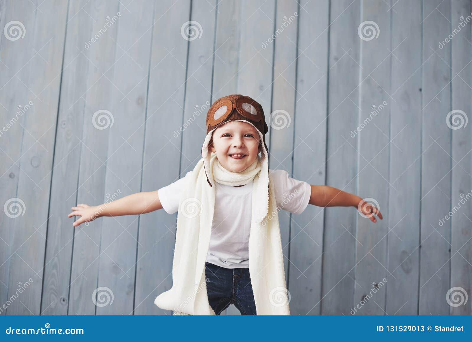 Härligt le barn i hjälm på en blå bakgrund som spelar med en nivå Pilot- begrepp för tappning