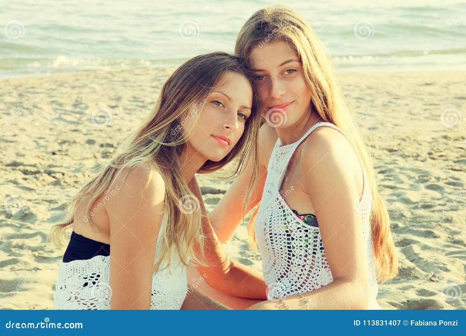 Härligt le för flickor som är lyckligt på stranden på retro stil för solnedgång