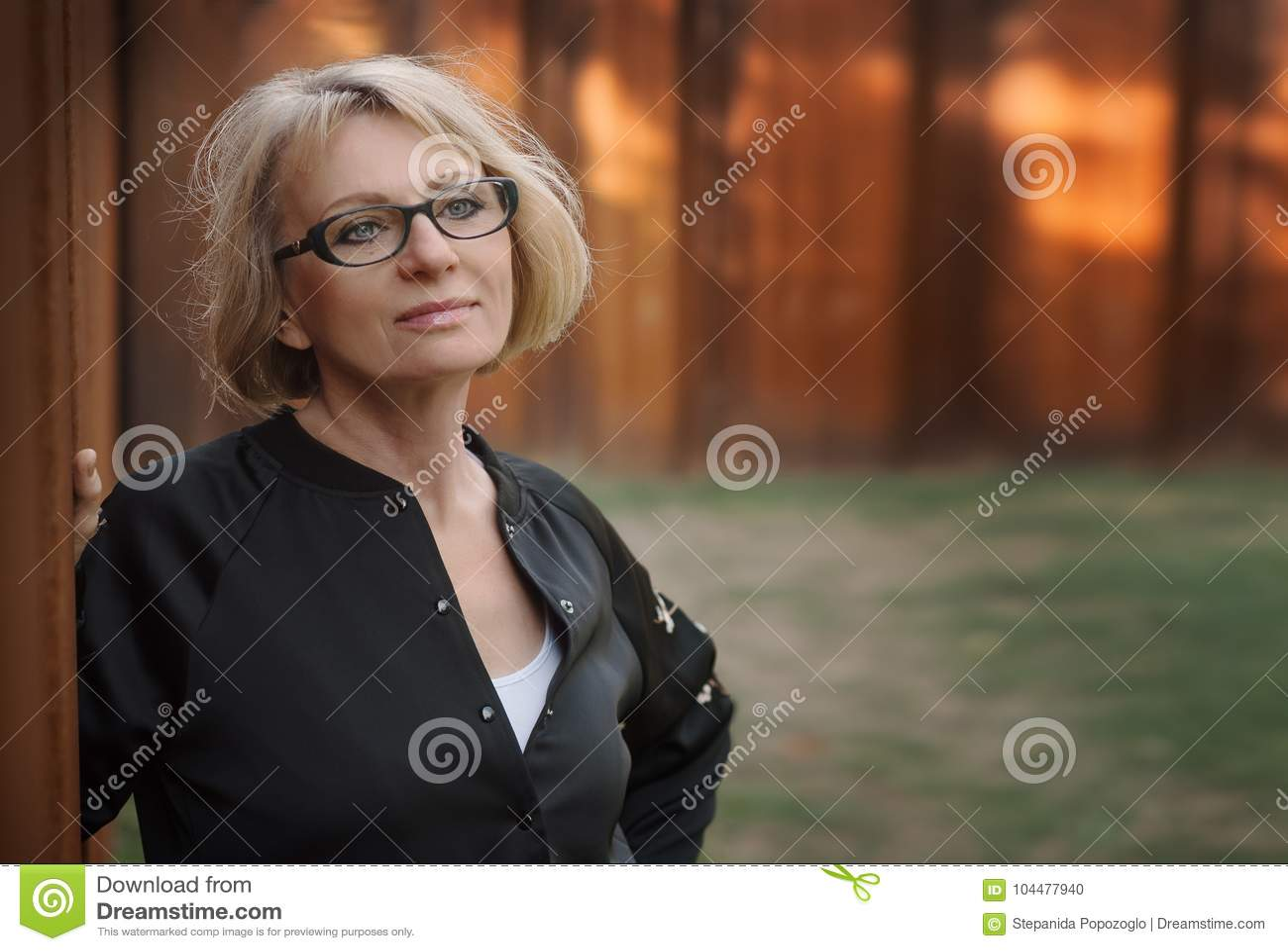 Härligt medelålderst kvinnaanseende vid väggen i parkera Ph