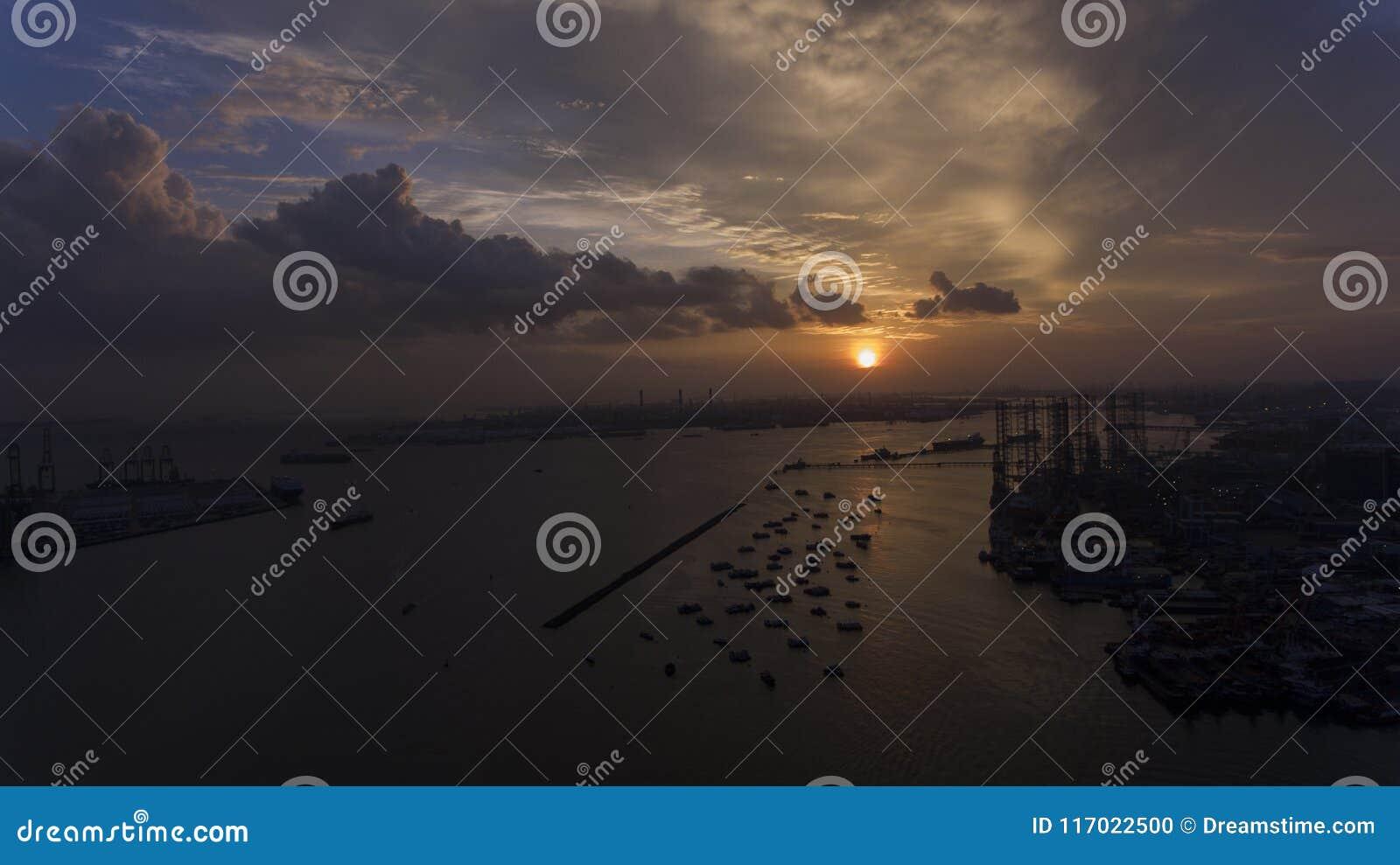 Härligt och att bedöva solnedgång över vattnet, över fartyg i en industriell seende skeppsdocka eller port