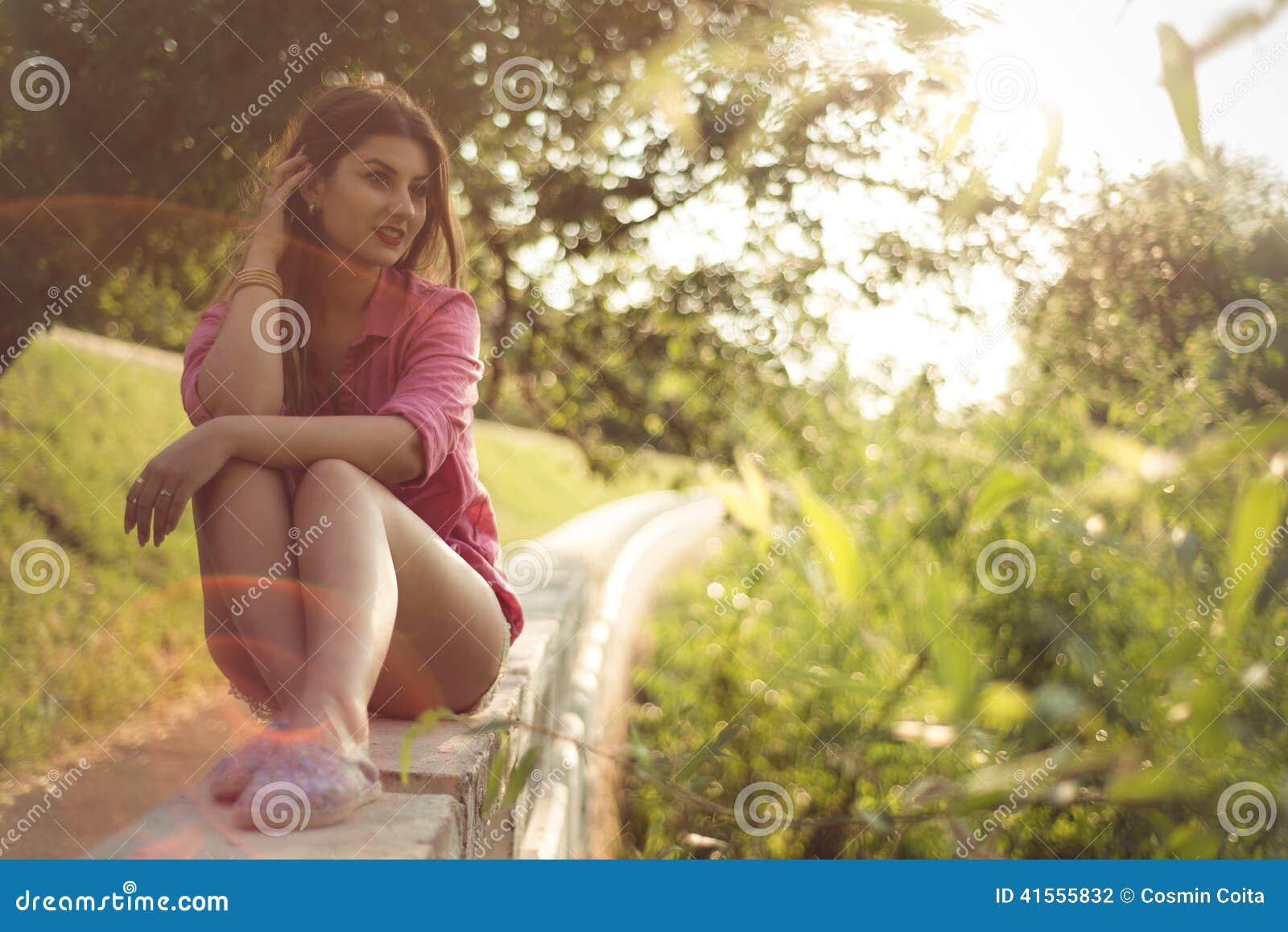 Härligt och attraktivt kvinnasammanträde på en sida, bärande sexig tillfällig grov bomullstvill kortsluter