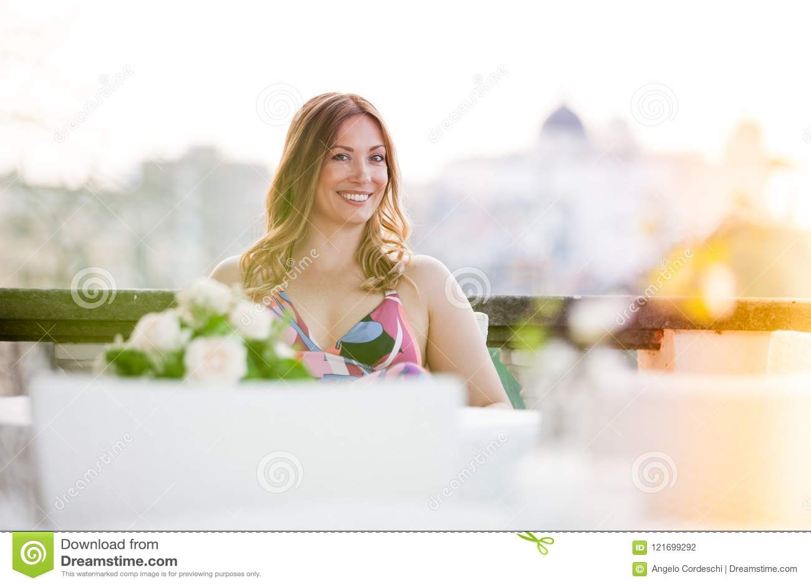 Härligt och charma le att sitta för kvinna som är utomhus-