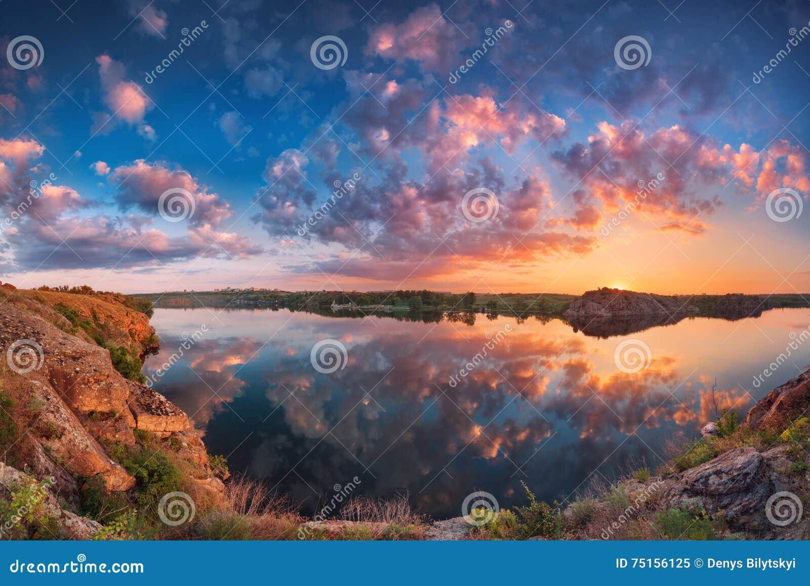 Härligt panorama- landskap med färgrik molnig himmel, sjö och