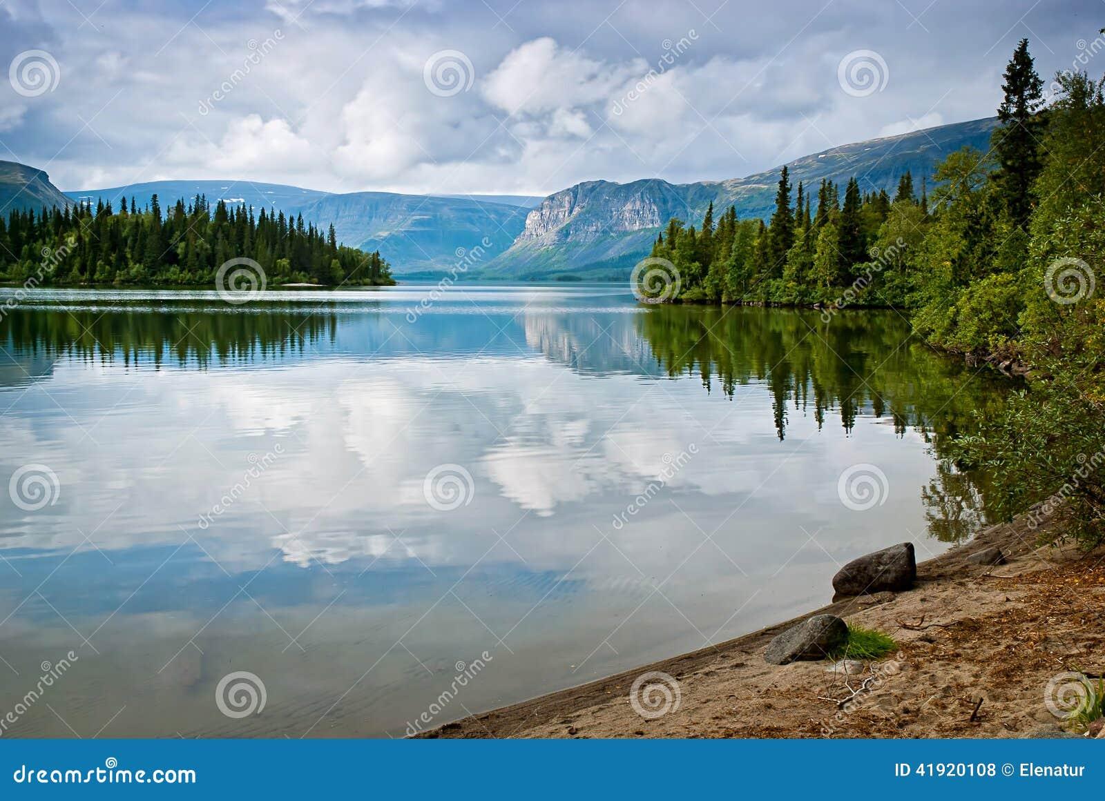 Härligt stillsamt landskap med berg och reflexion av cl