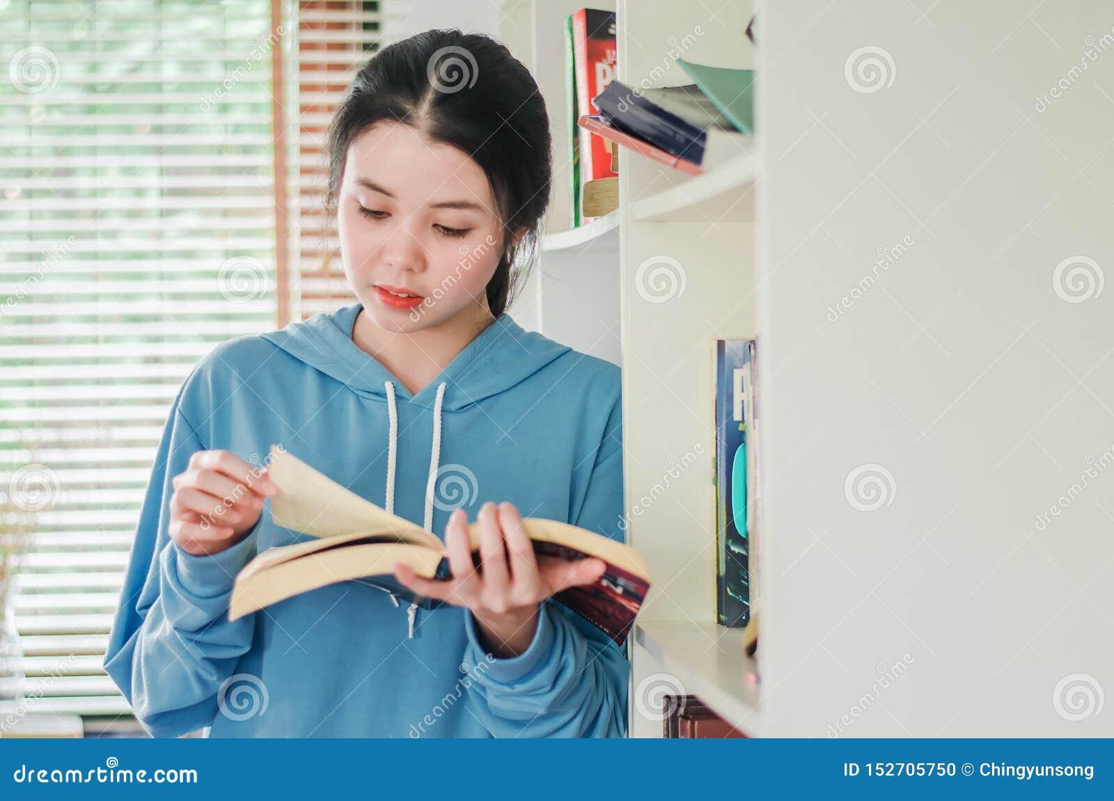 Härligt ung flickaanseende i arkivet hemma med böcker, kvinna som läser en bok