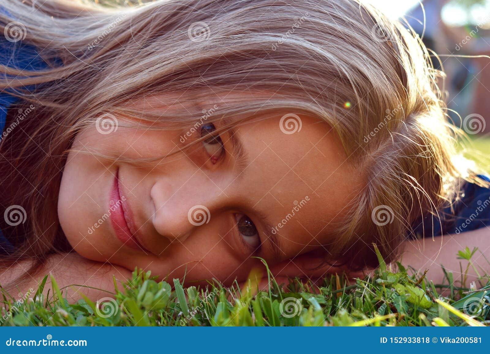 Härligt ung flickaslut upp på grönt gräs i sommar Le den unga framsidan av flickan