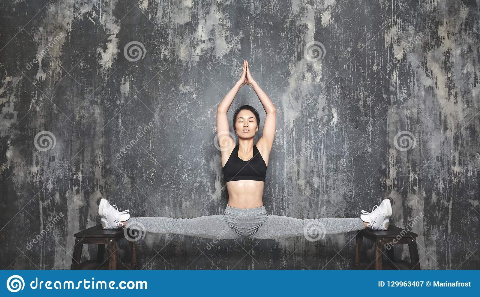 Härligt ungt asiatiskt utarbeta för kvinna som gör den Pilates övningen i Sportswear Splittringar med yoga Asana som sträcker