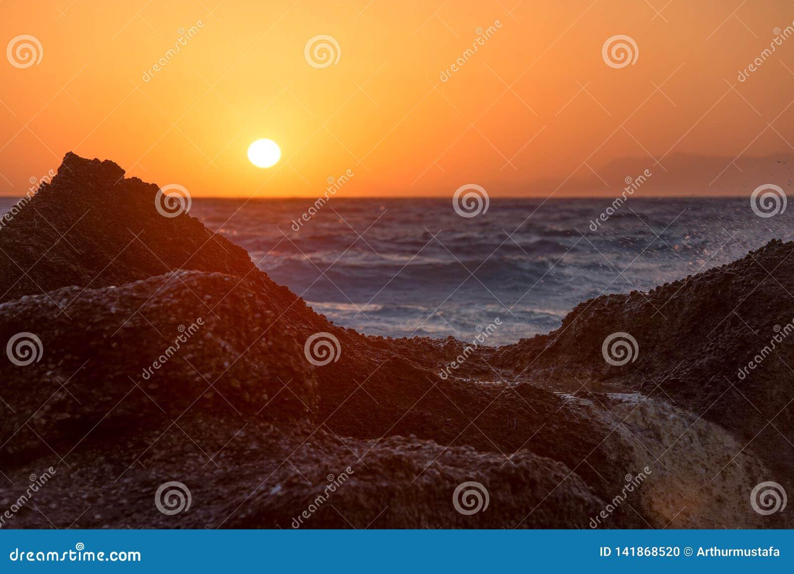 Härligt varmt solnedgångljus som glöder över en stenig tropisk strand