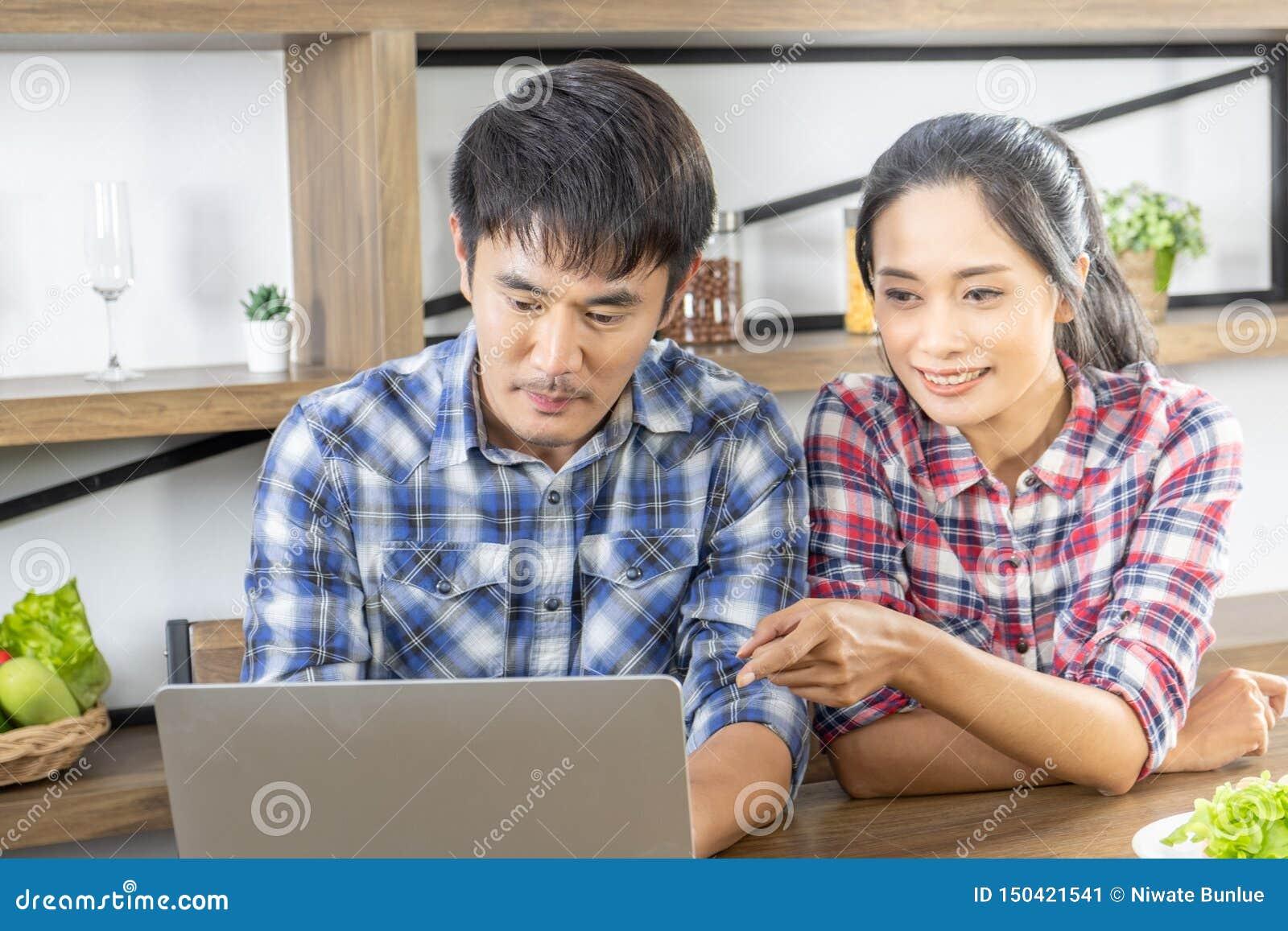Hållande ögonen på bärbar dator för unga asiatiska älskvärda par för att shoppa direktanslutet
