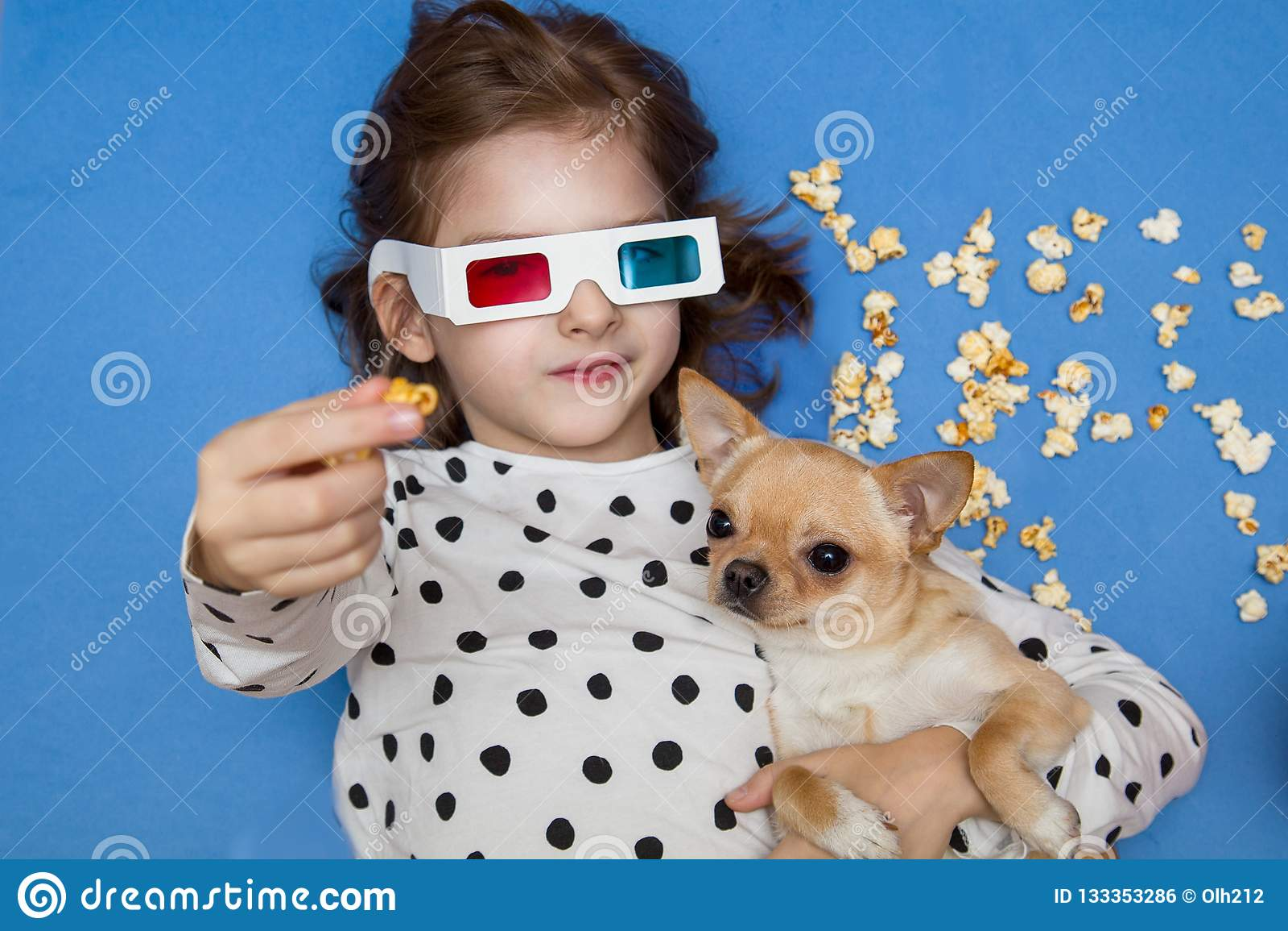 Hållande ögonen på film för flicka och för liten hund i exponeringsglas 3D med popcorn