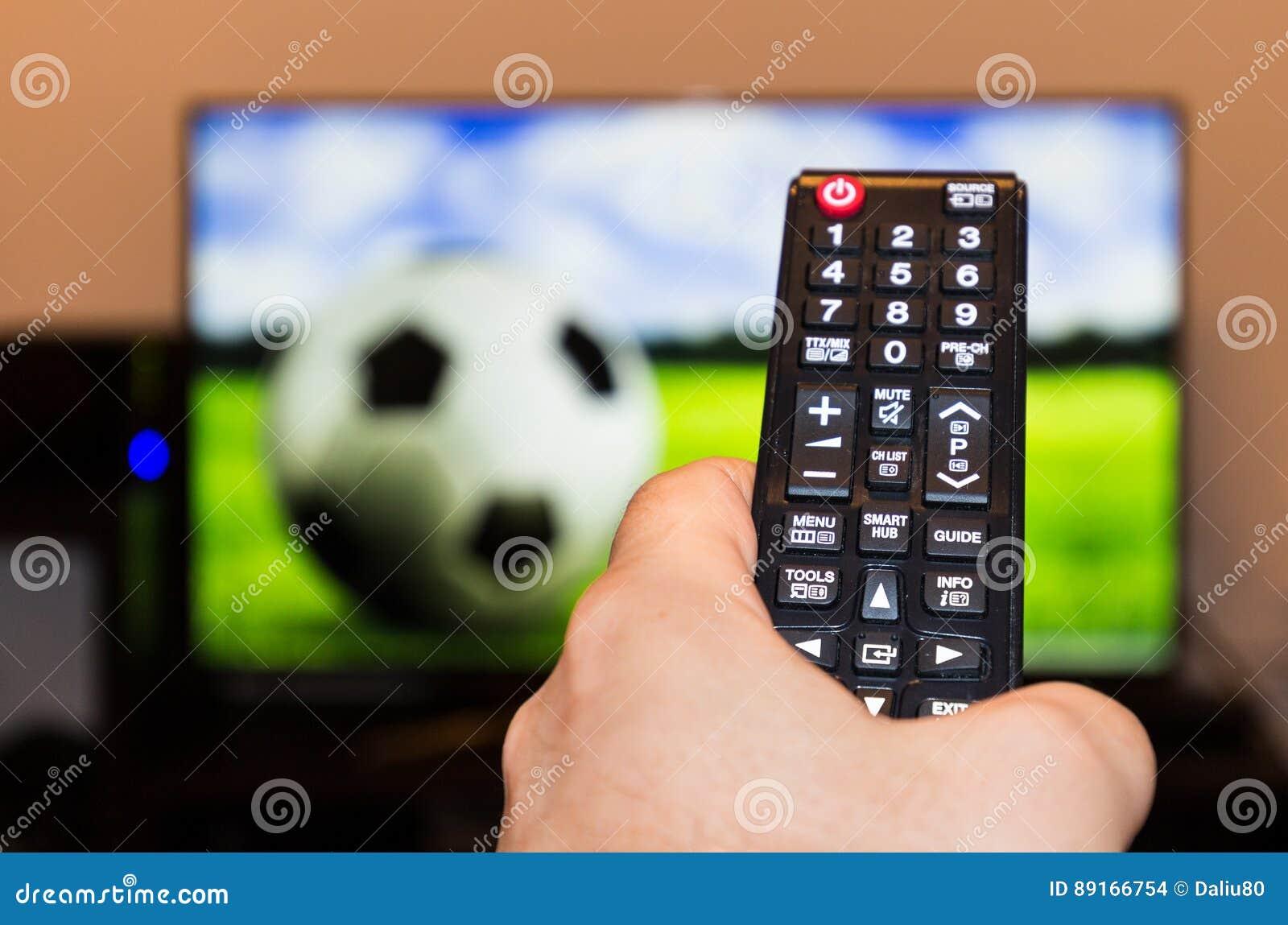 Hållande ögonen på fotboll-/fotbolllek på modern tv, med en närbild av
