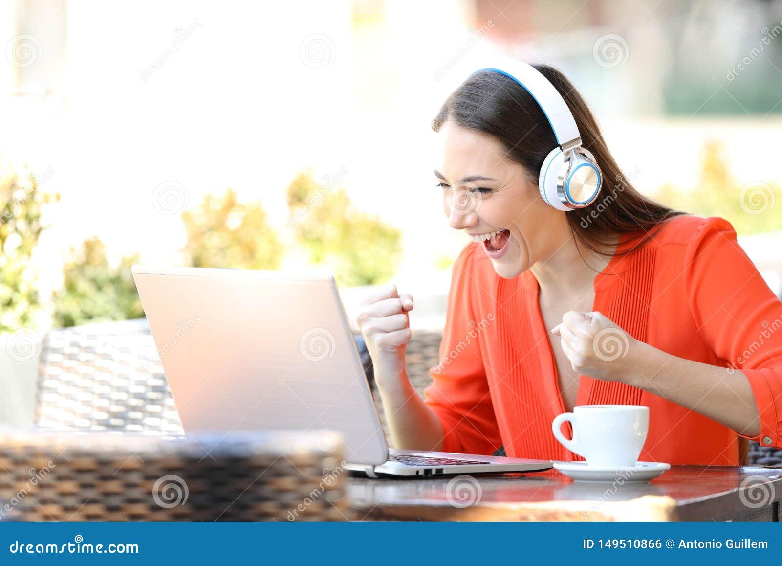 H?llande ?gonen p? och lyssnande massmedia f?r upphetsad kvinna p? b?rbara datorn