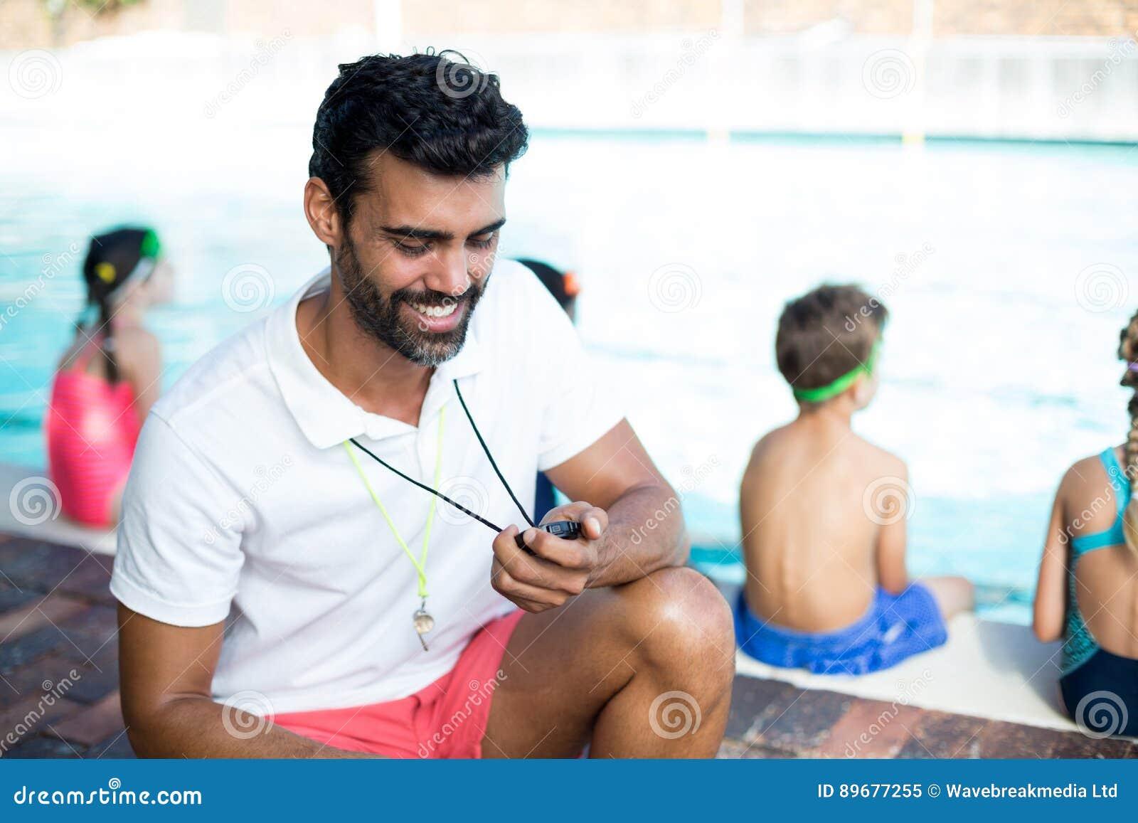 Hållande ögonen på stoppur för manlig instruktör av barn på poolsiden