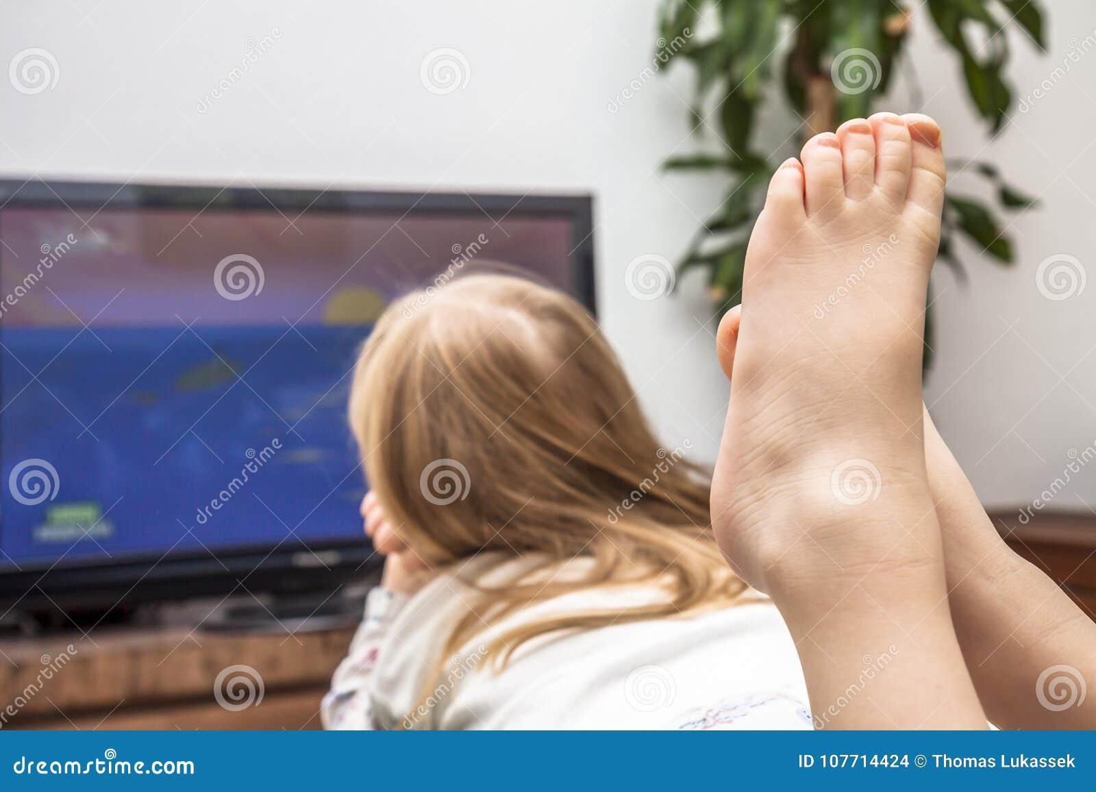 Hållande ögonen på television för liten flicka på soffan