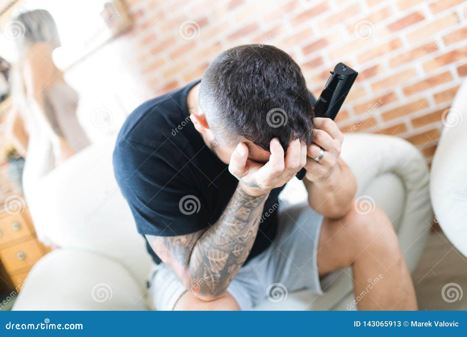 Hållande ögonen på television för olycklig man, framsida i händer