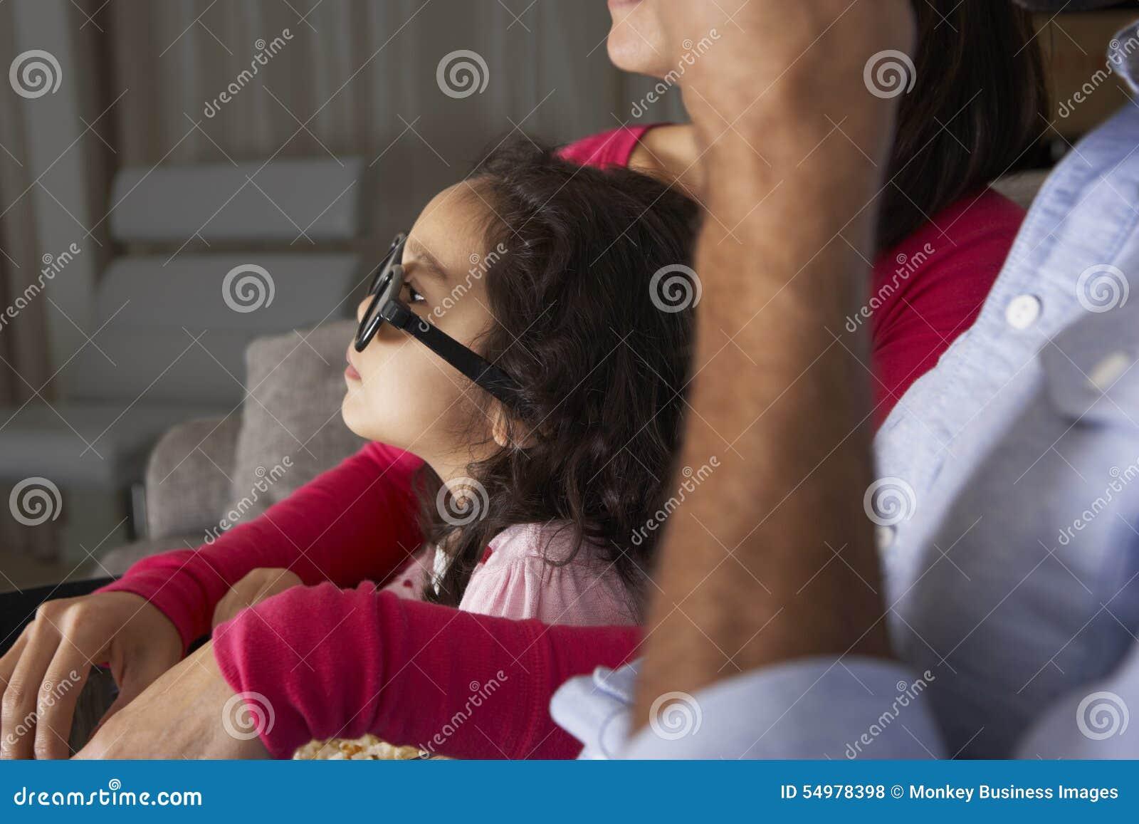 Hållande ögonen på TV för familj som bär exponeringsglas 3D och äter popcorn