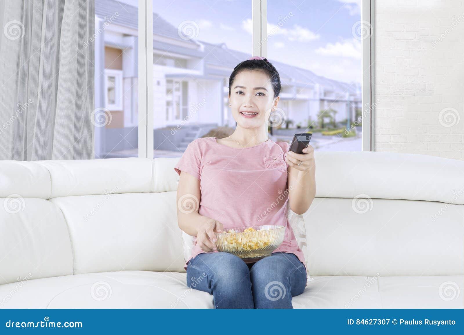 Hållande ögonen på tv för nätt kvinna på soffan