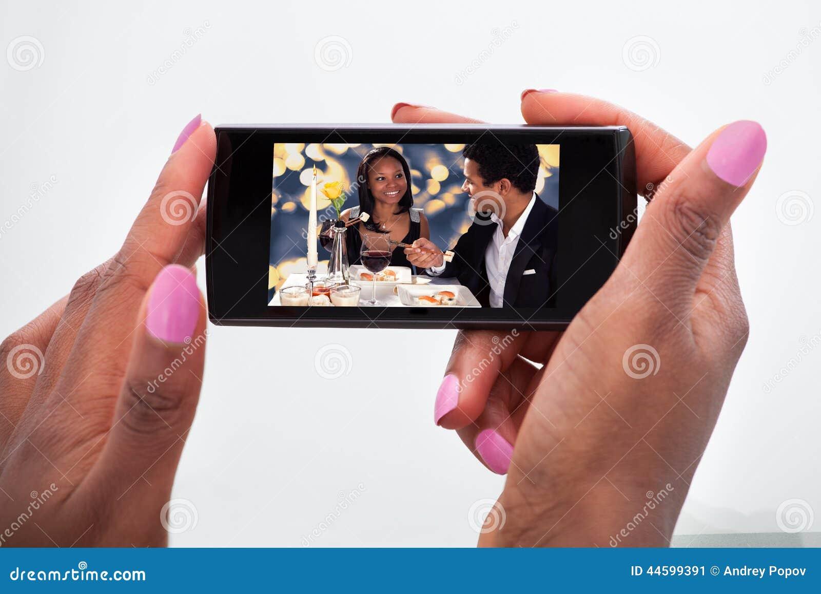 Hållande ögonen på video för kvinna på mobiltelefonen hemma