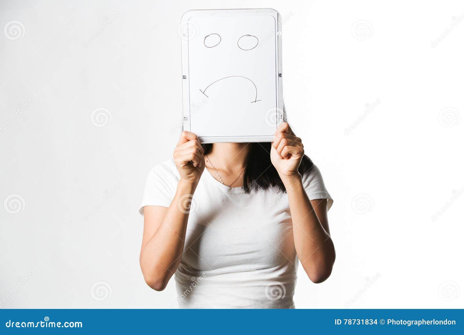 Hållande övre för kinesisk kvinna ett vitt bräde med en ledsen framsida som dras på den