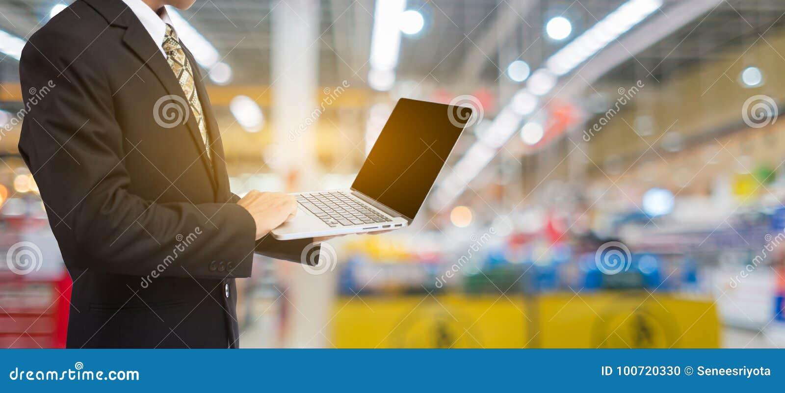 Hållande bärbar dator för affärsmanhand i suddighetssupermarket