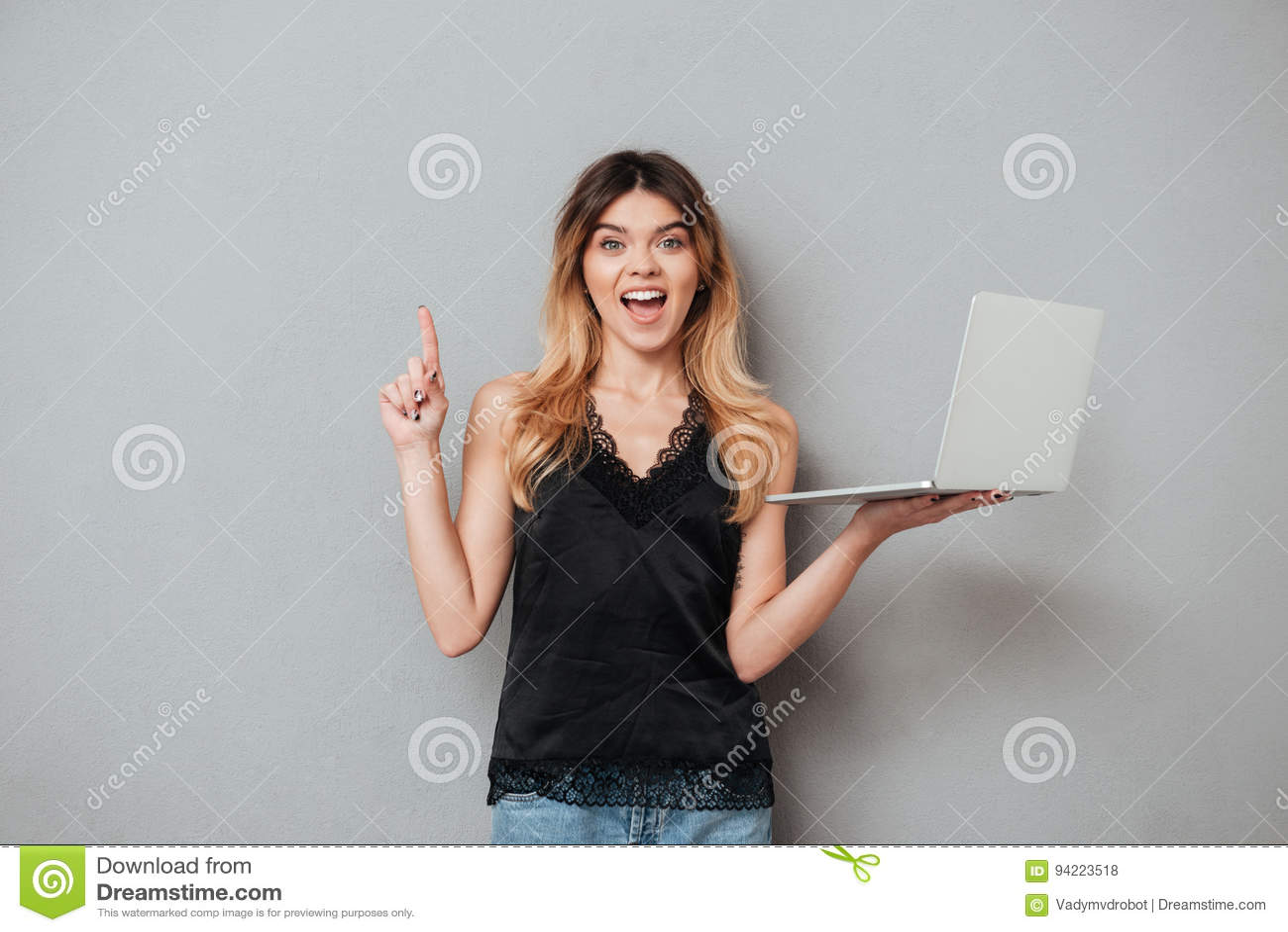 Hållande bärbar dator för upphetsad flicka och pekafinger upp på copyspace
