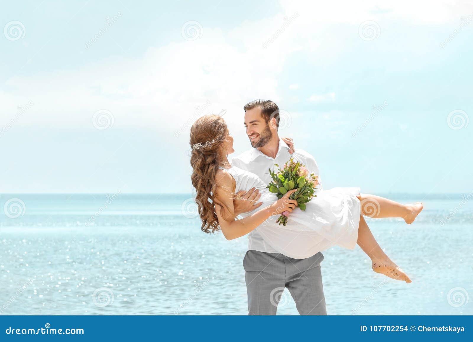 Hållande brud för lycklig brudgum i hans armar