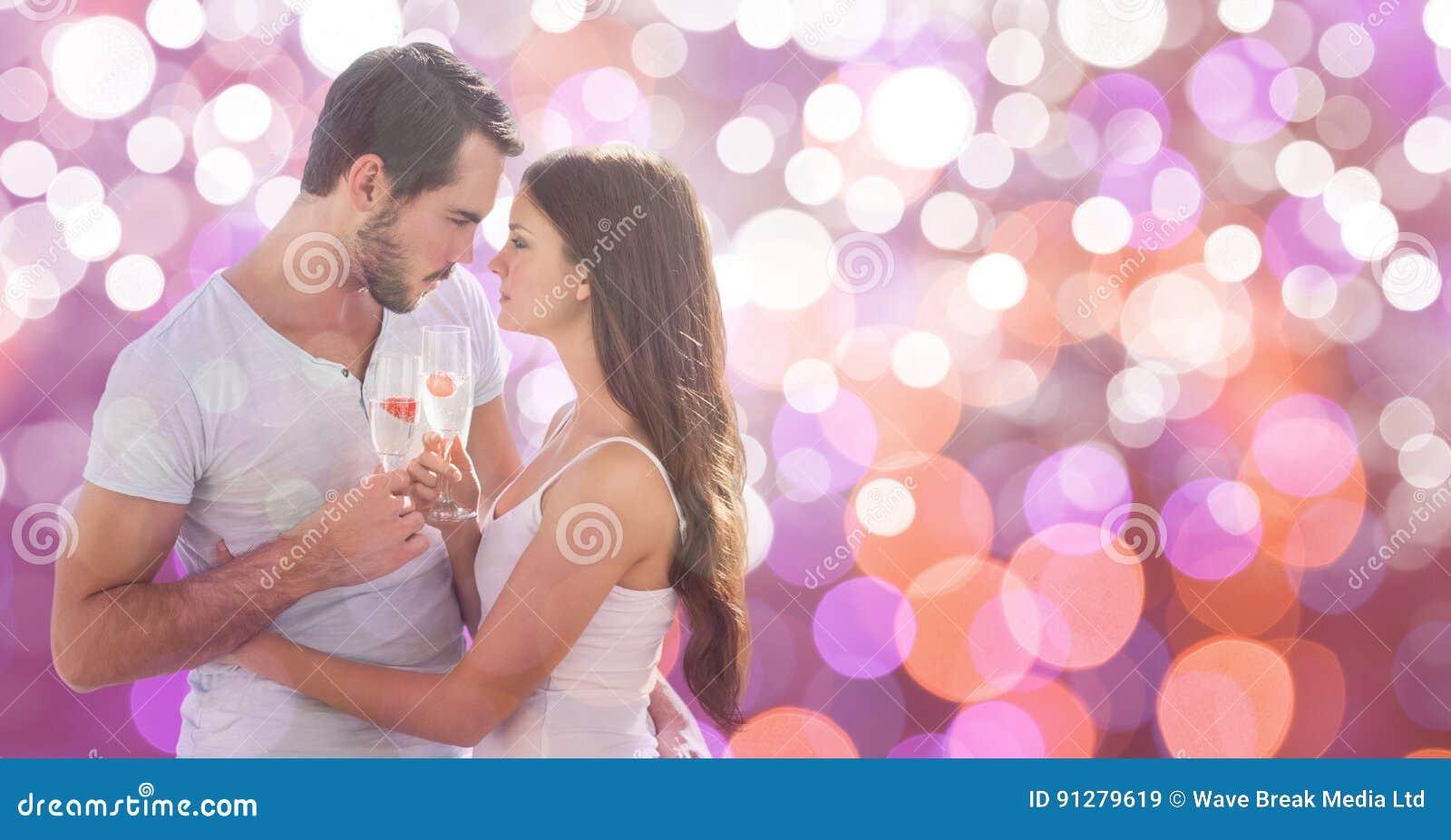 Hållande champagneflöjter för passionerade par över bokeh