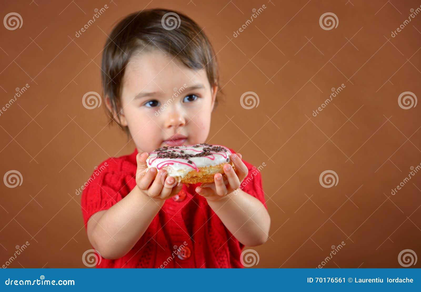 Hållande donuts för liten flicka