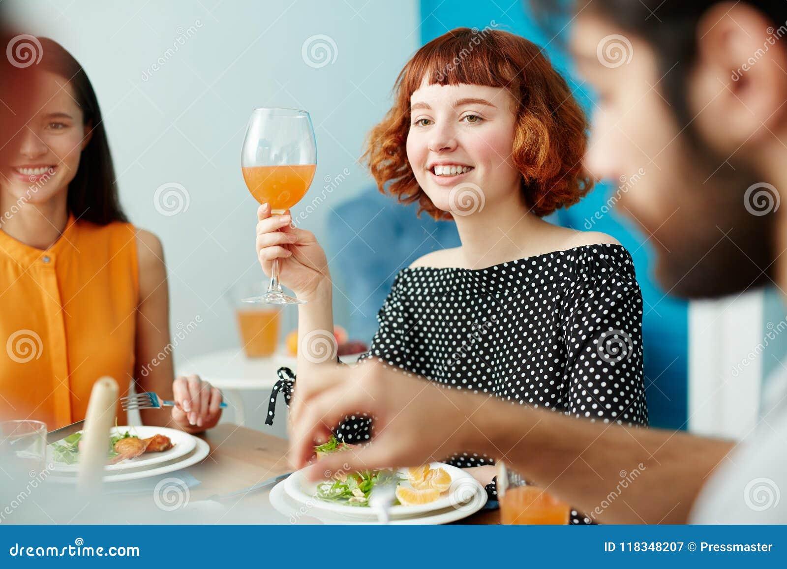Hållande exponeringsglas för härlig kvinna, medan äta med vänner
