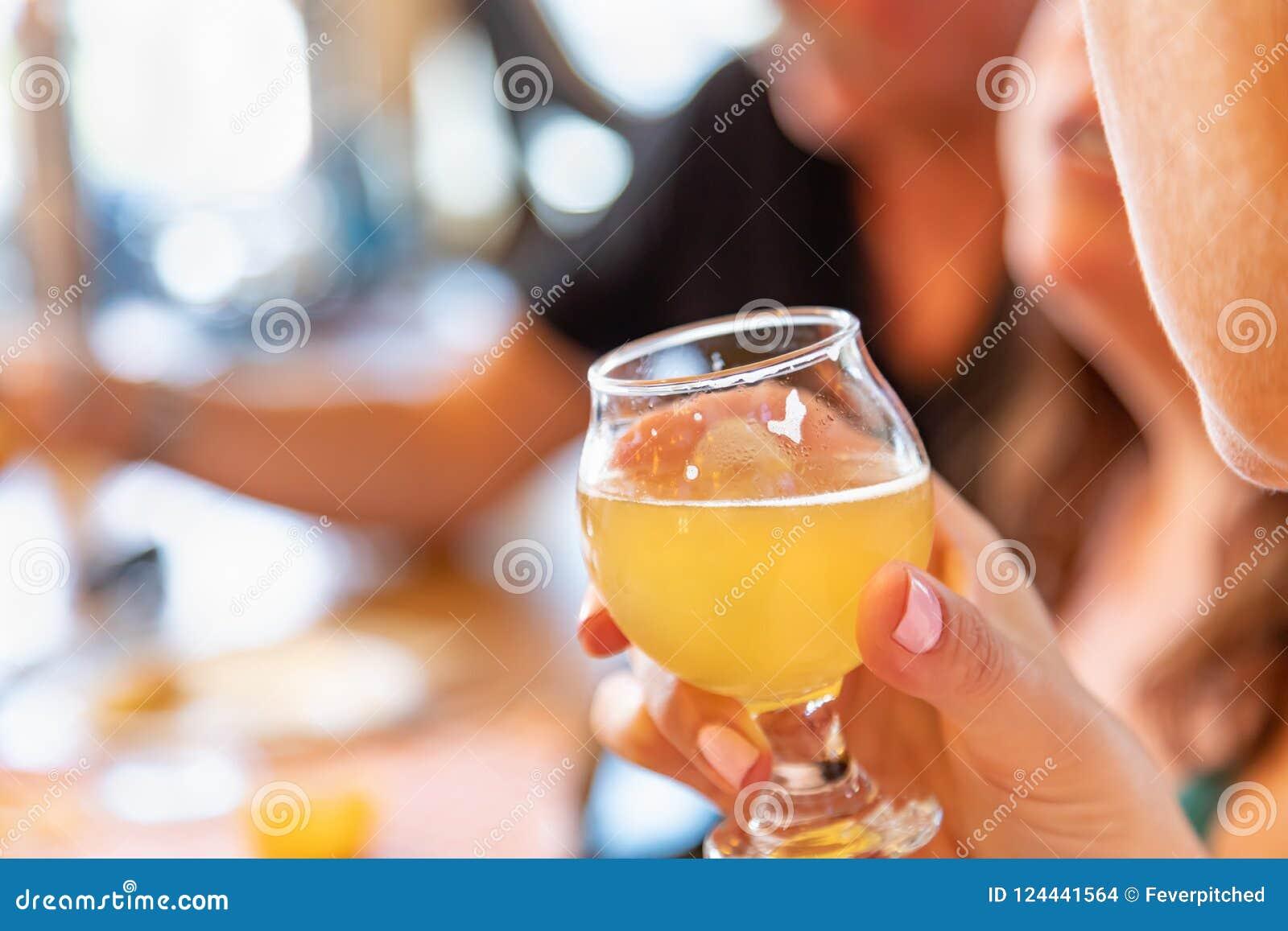 Hållande exponeringsglas för kvinnlig hand av mikrobrygdöl på stången