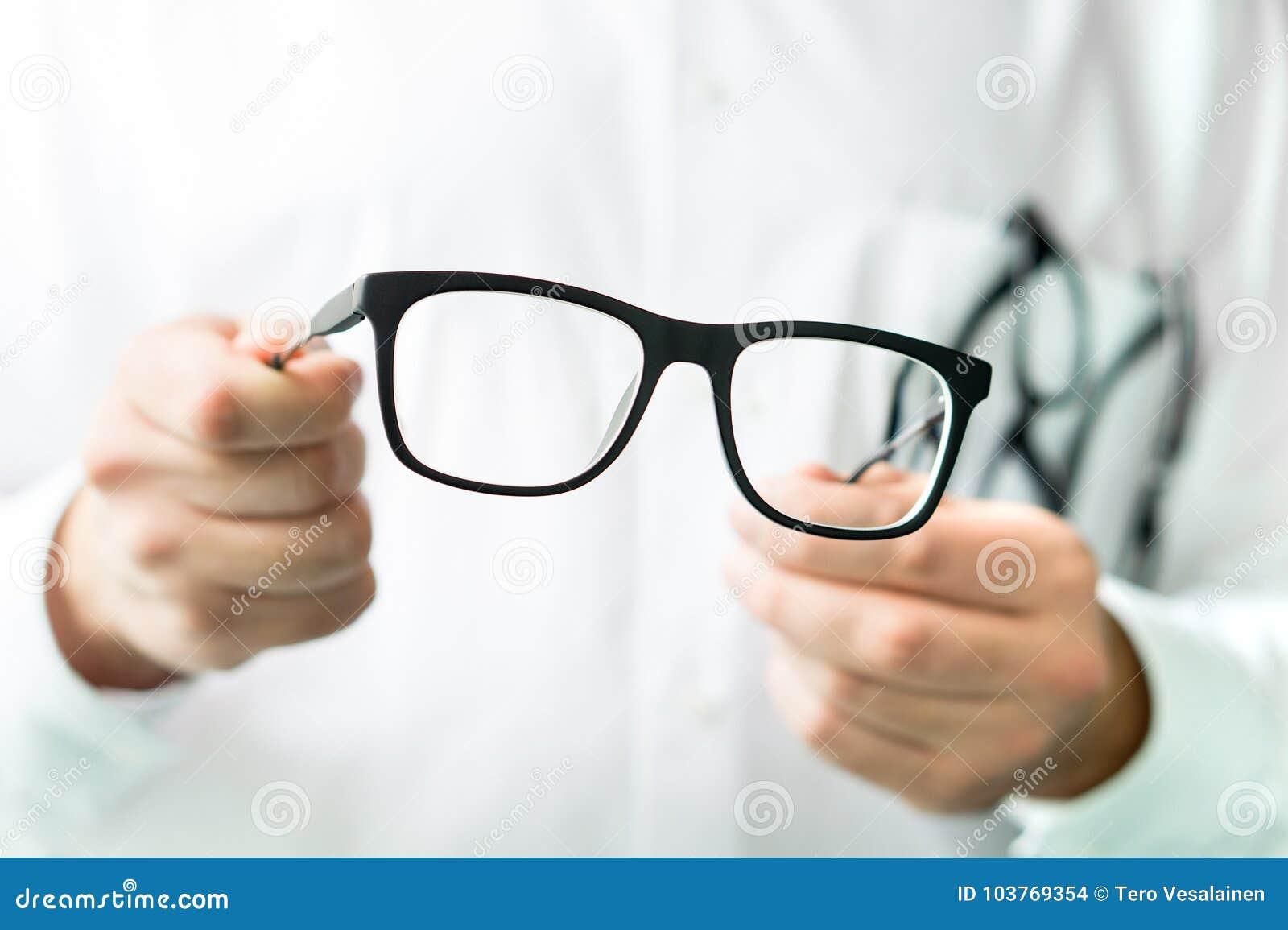 Hållande exponeringsglas för optiker Ögondoktor som visar nya linser