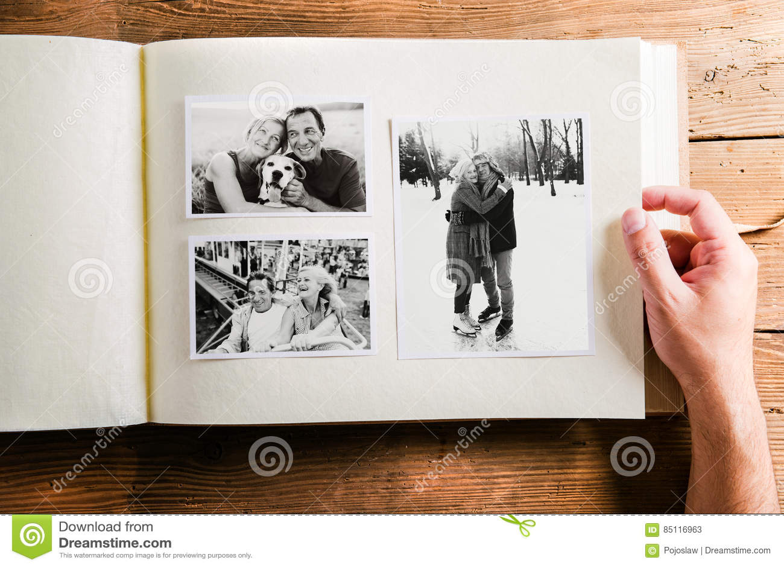 Hållande fotoalbum för hand med bilder av höga par studio