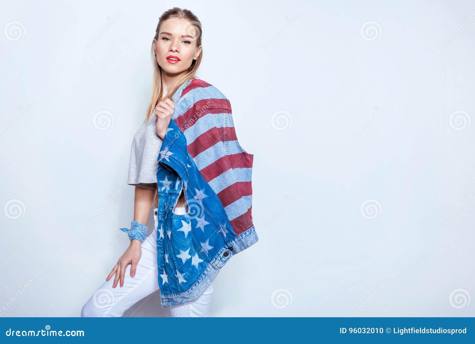 Hållande grov bomullstvillväst för blond flicka med amerikanska flaggan på skuldra och se kameran