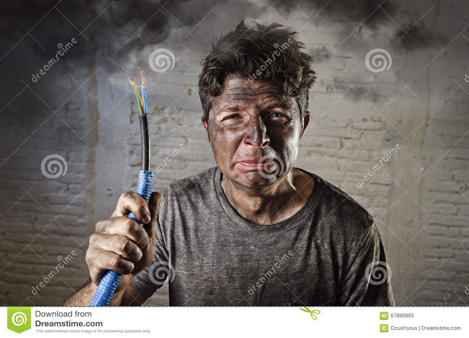 Hållande kabel för ung man som röker efter elektrisk olycka med den smutsiga brända framsidan i roligt ledset uttryck