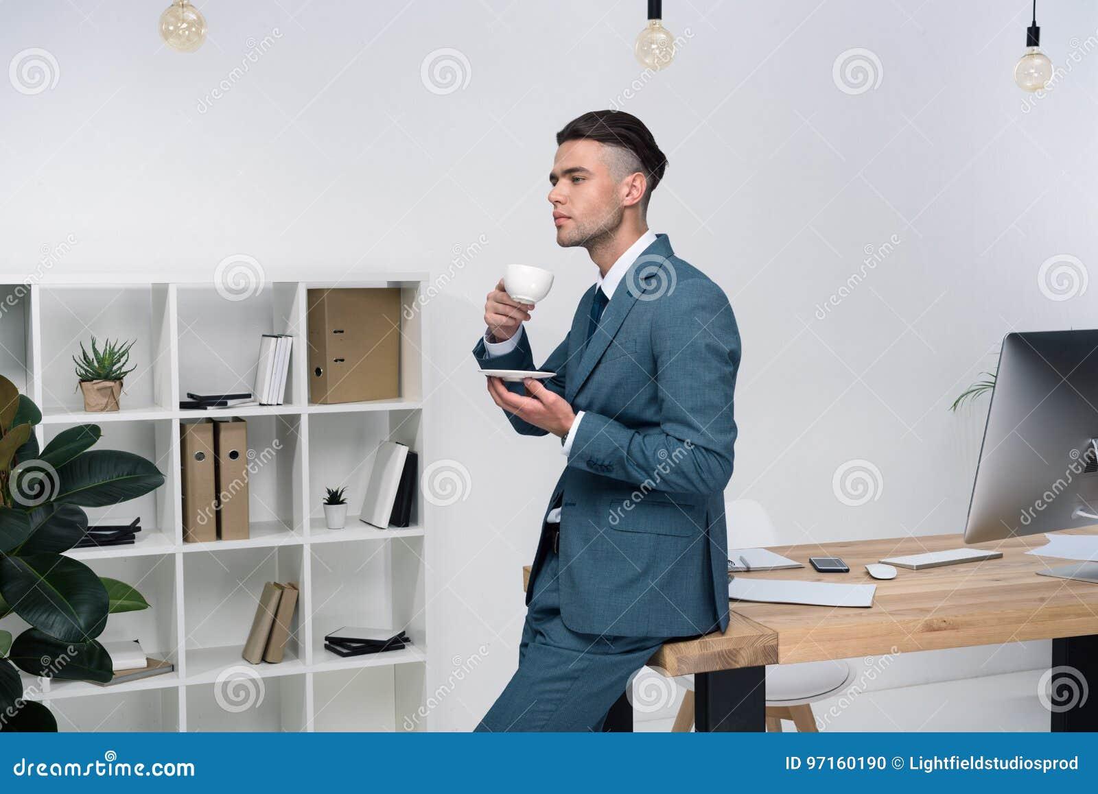Hållande kopp kaffe för ung affärsman, medan sitta på kontorstabellen och se bort