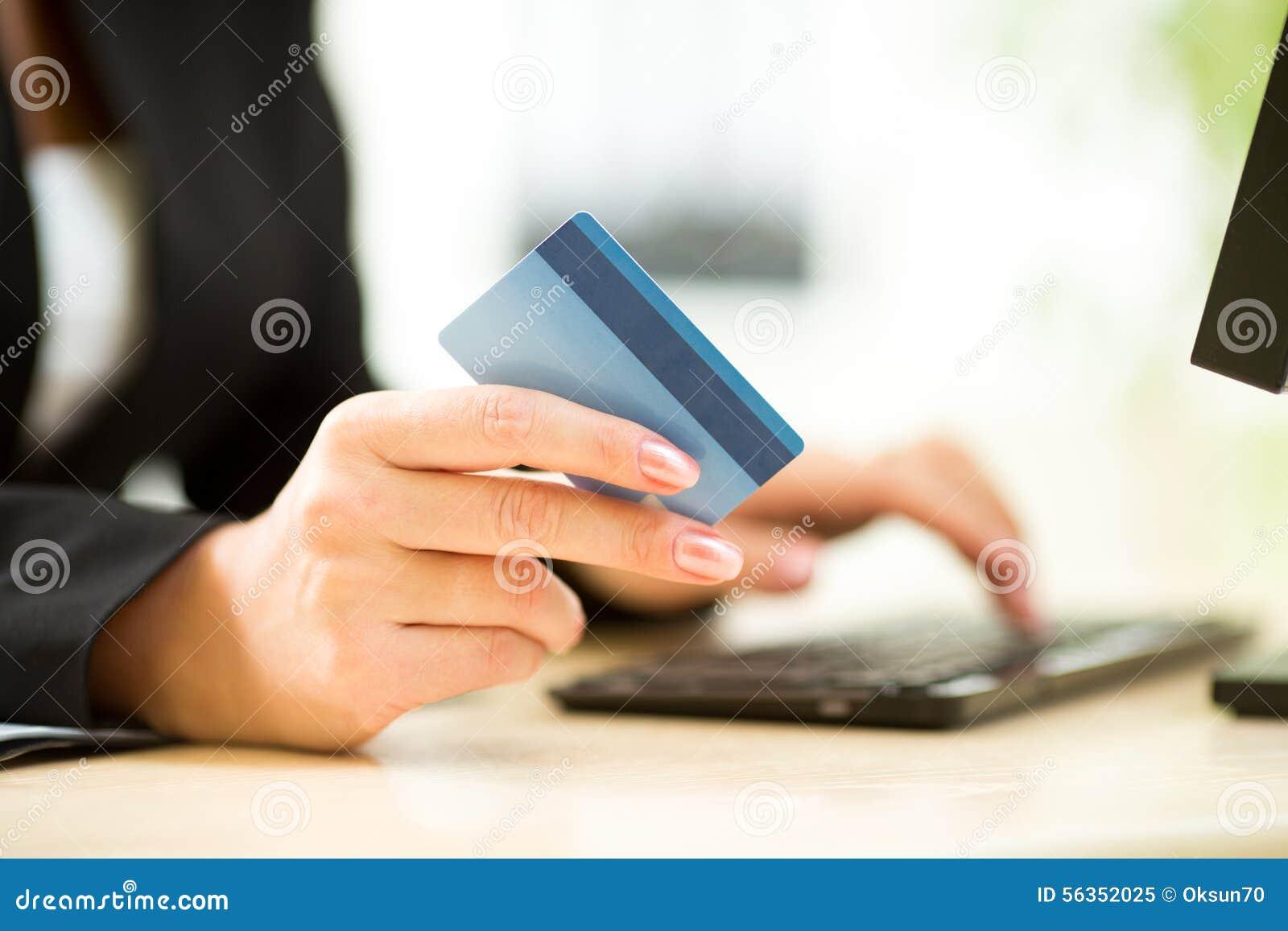 Hållande kreditkort för affärskvinna på bärbara datorn för online-betalningbegrepp