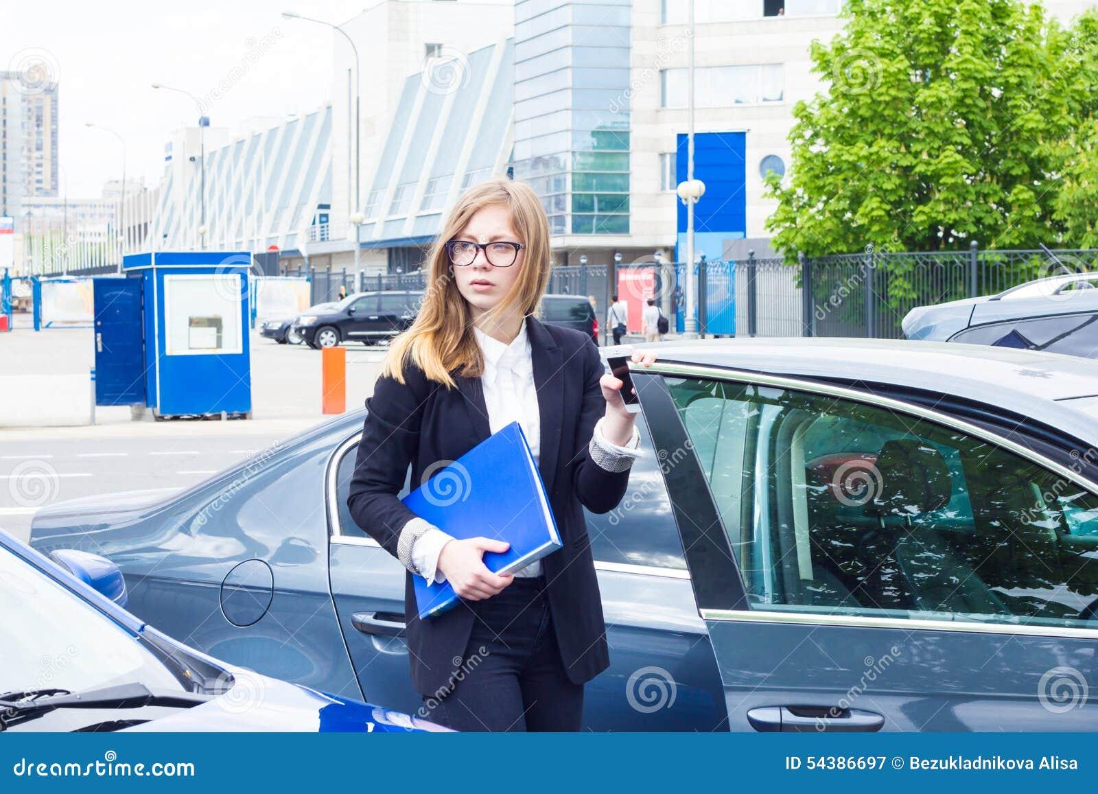 Hållande mapp för affärskvinna med dokument i och ut ur hennes bil