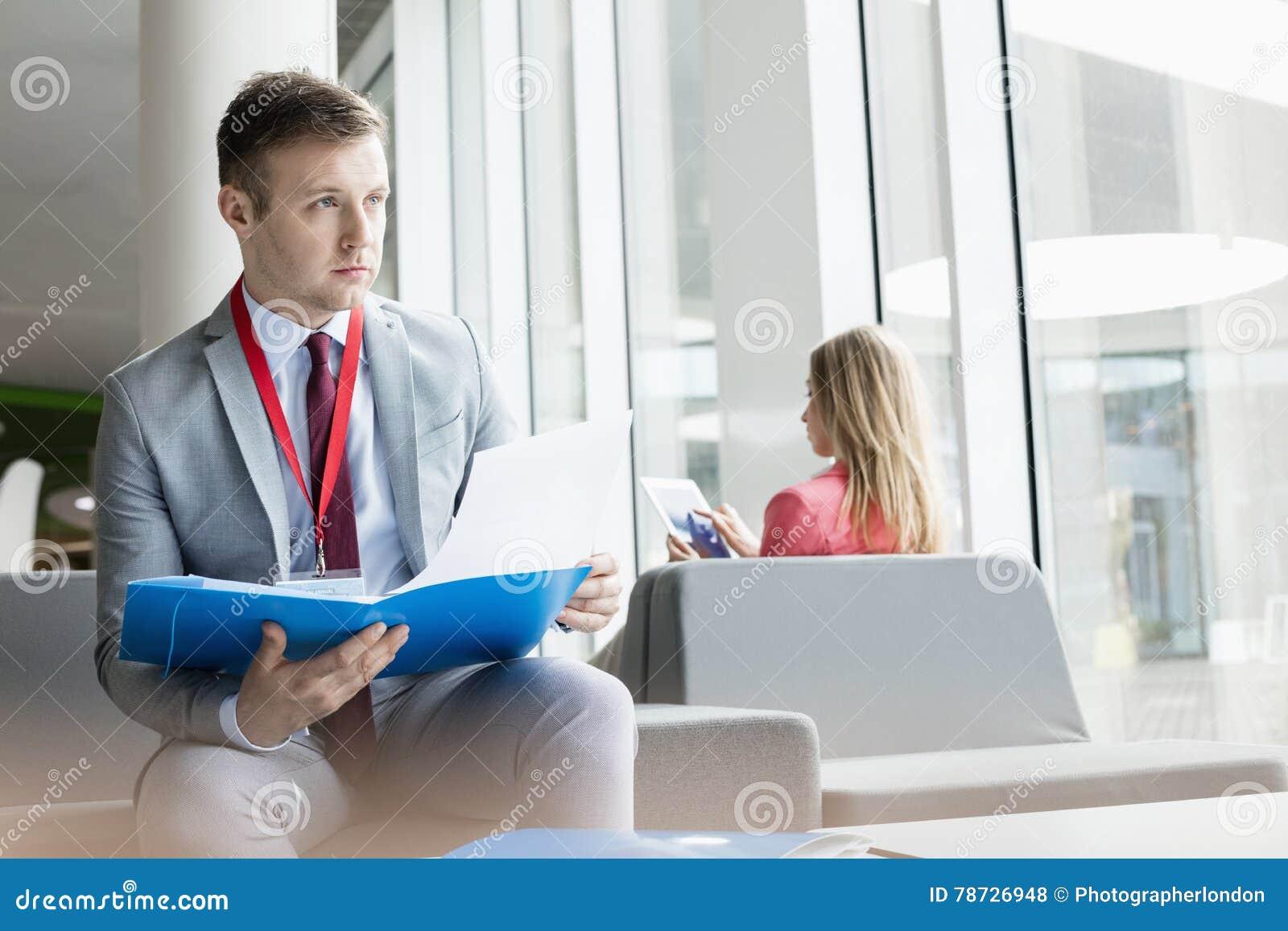 Hållande mapp för fundersam affärsman, medan sitta på lobbyen i konventcentrum