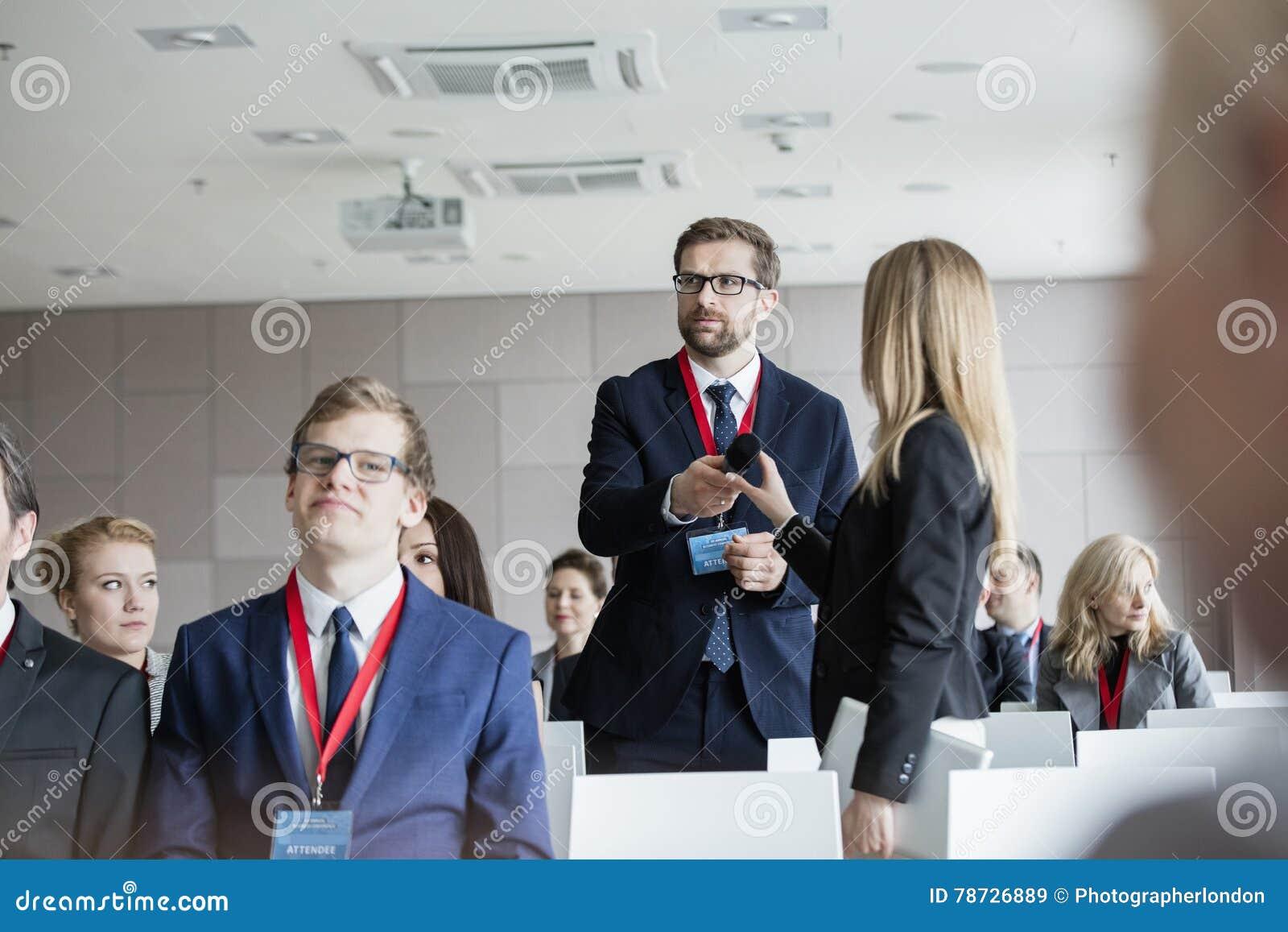 Hållande mikrofon för affärsfolk, medan stå under seminarium