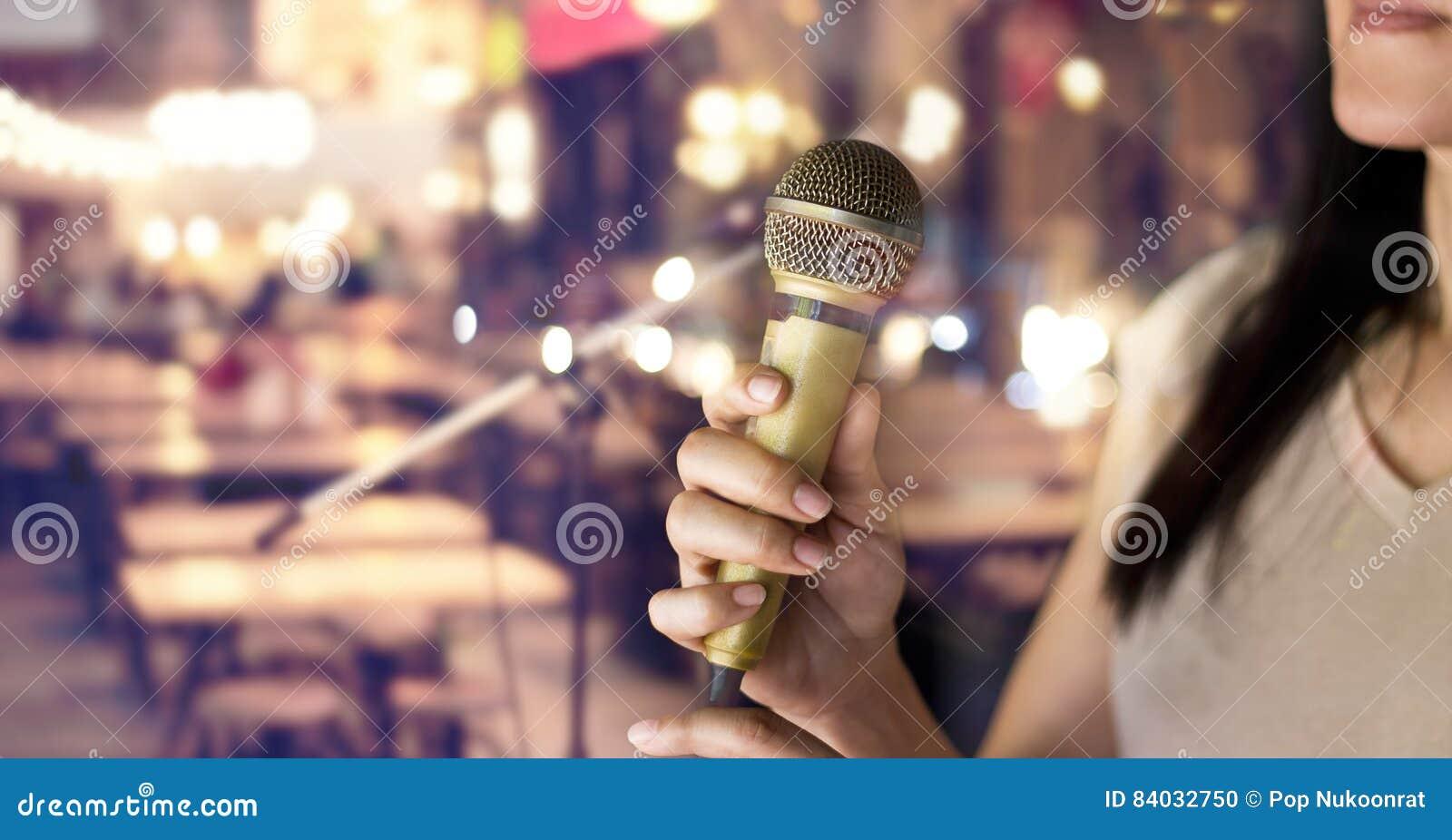 Hållande mikrofon för kvinna i hand på bar och restaurang