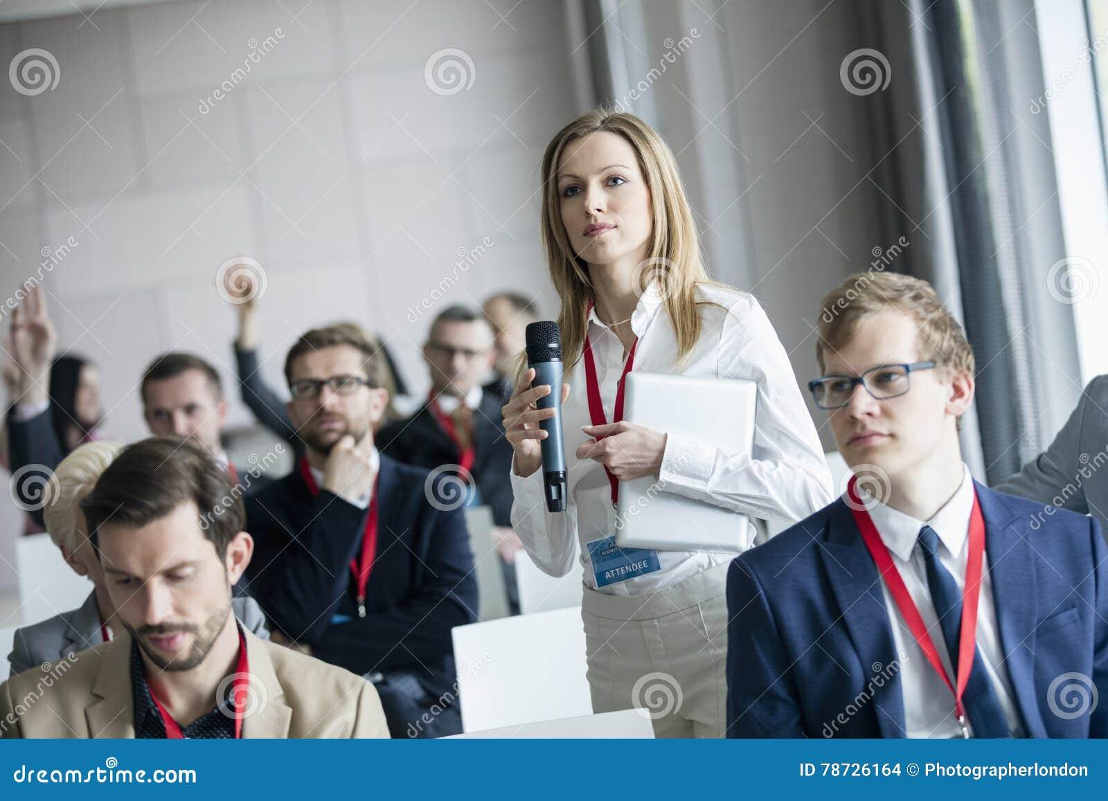 Hållande mikrofon för säker affärskvinna, medan fråga frågor under seminarium