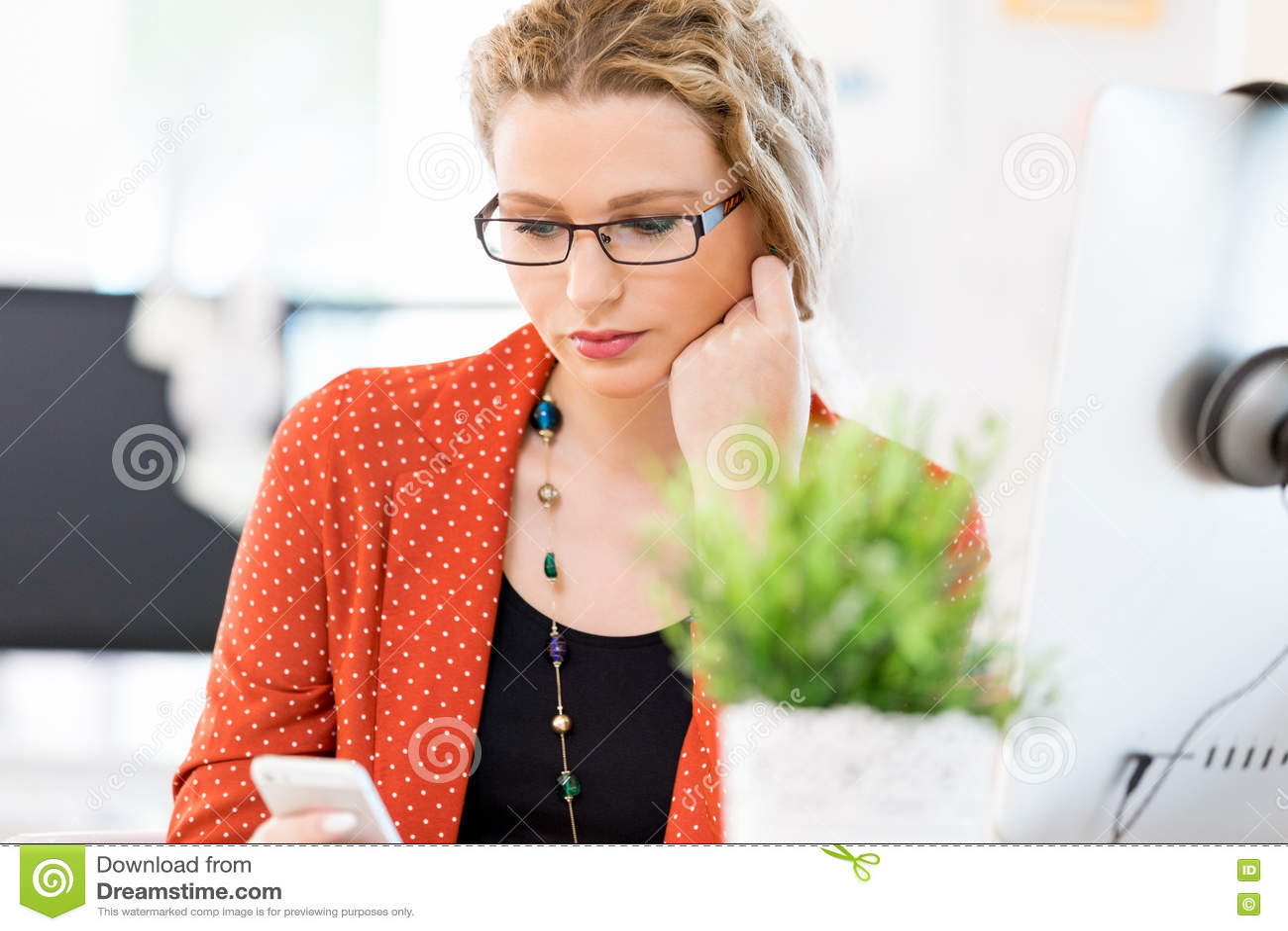 Hållande mobiltelefon för ung kvinna i regeringsställning