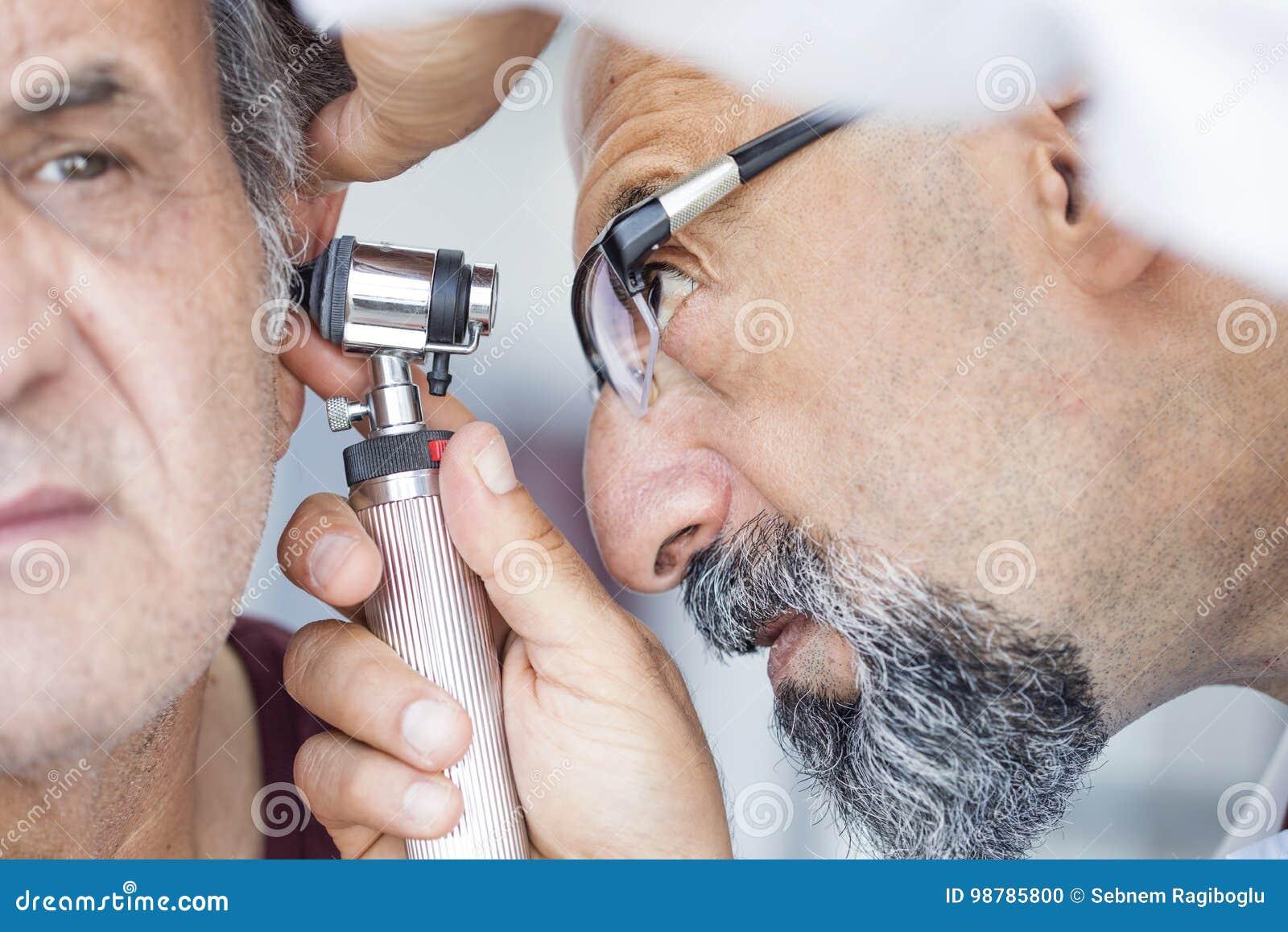 Hållande otoscope för doktor och undersökande öra av den höga mannen
