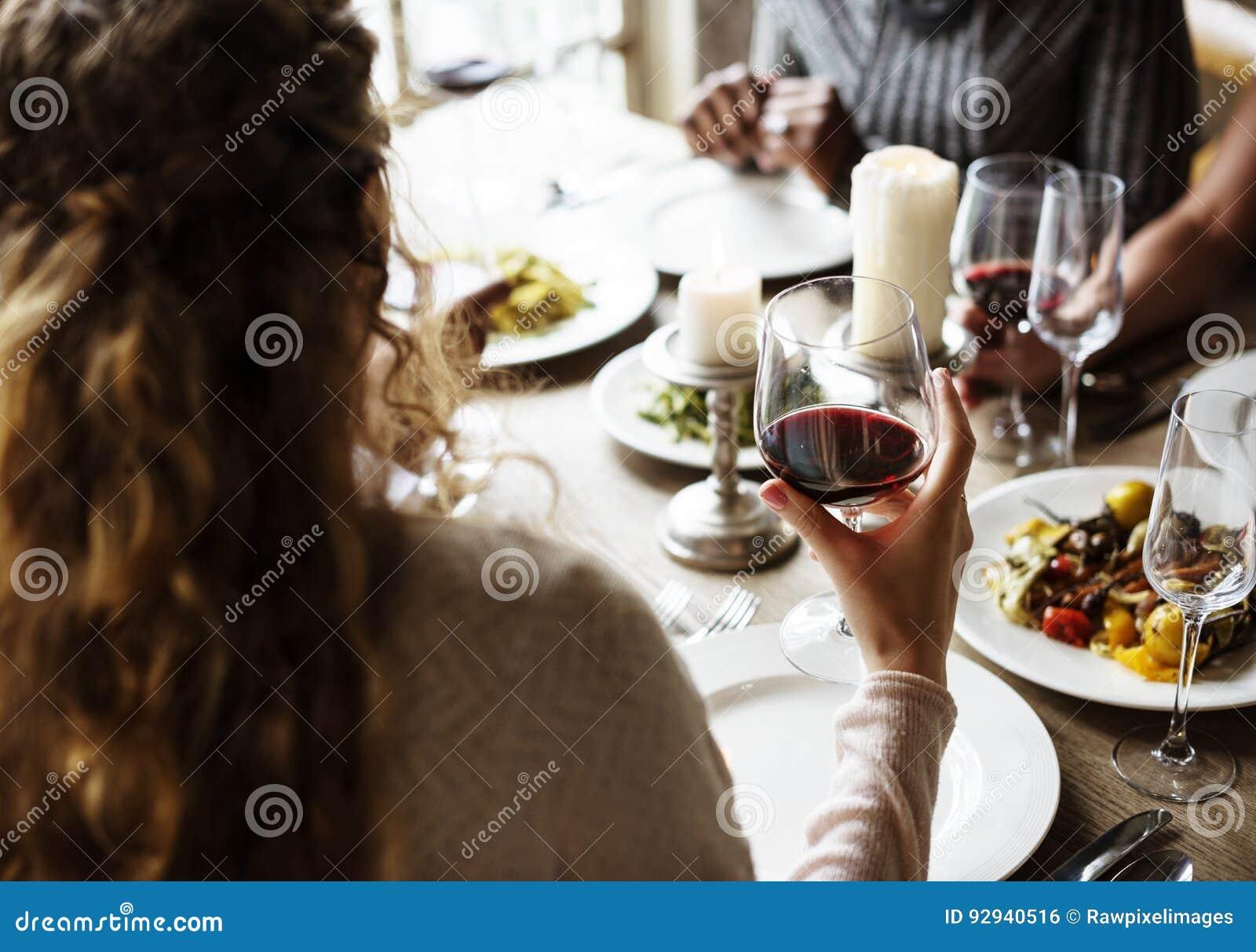 Hållande rött vinexponeringsglas för kvinna i en flott restaurang